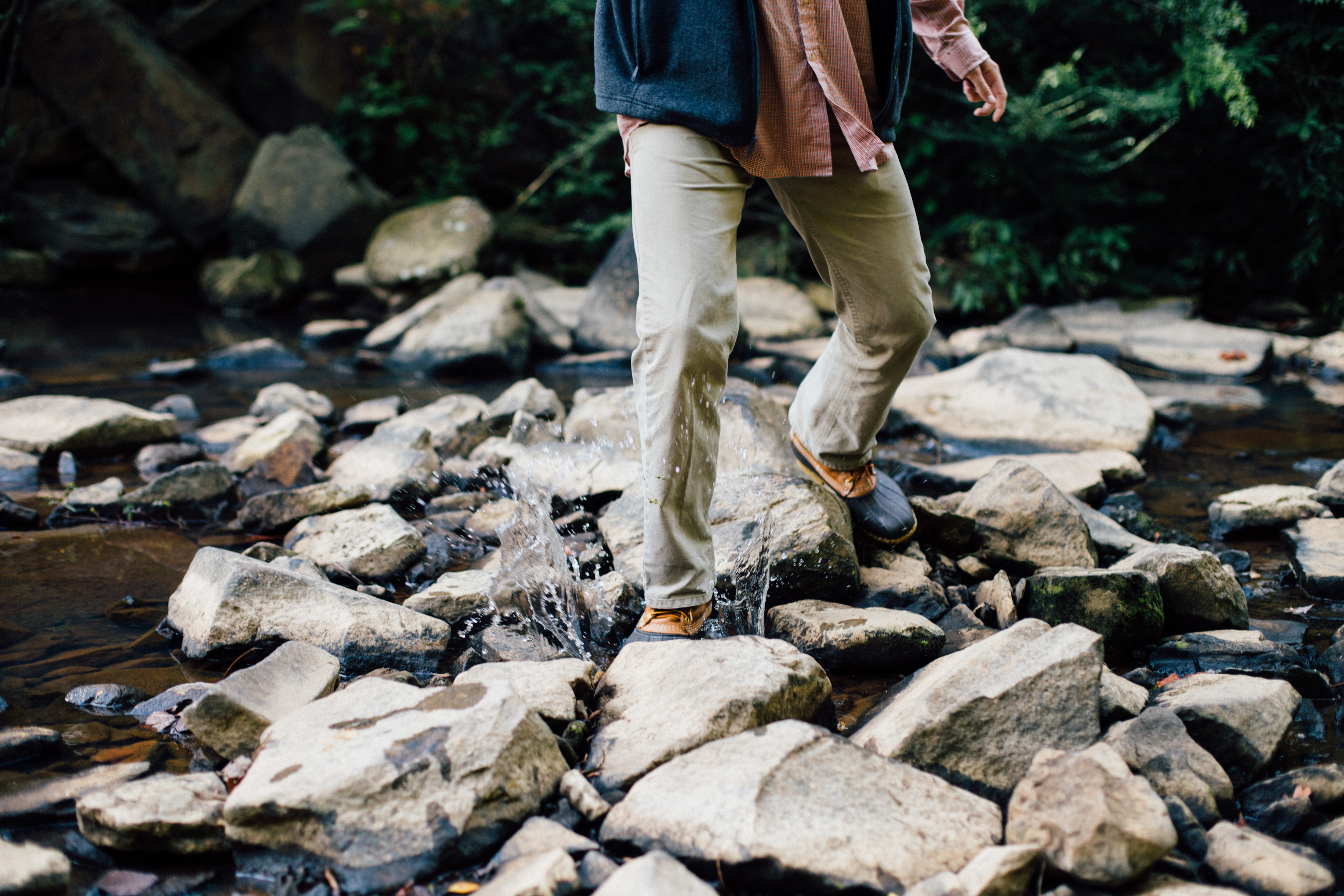 A man splashing across a stream in duck boots and a vest