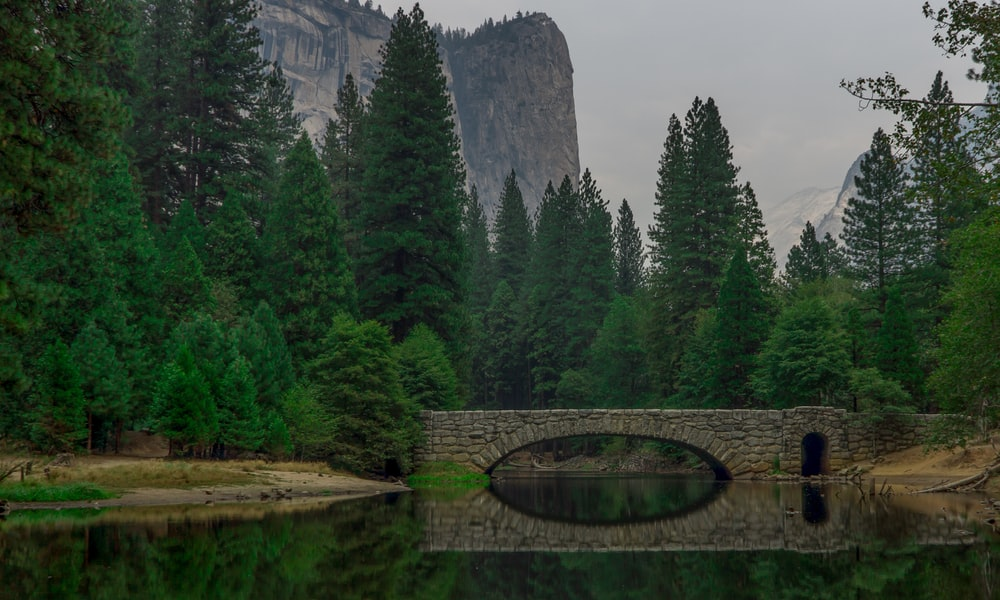 reflection of concrete bridge on river with mountain view