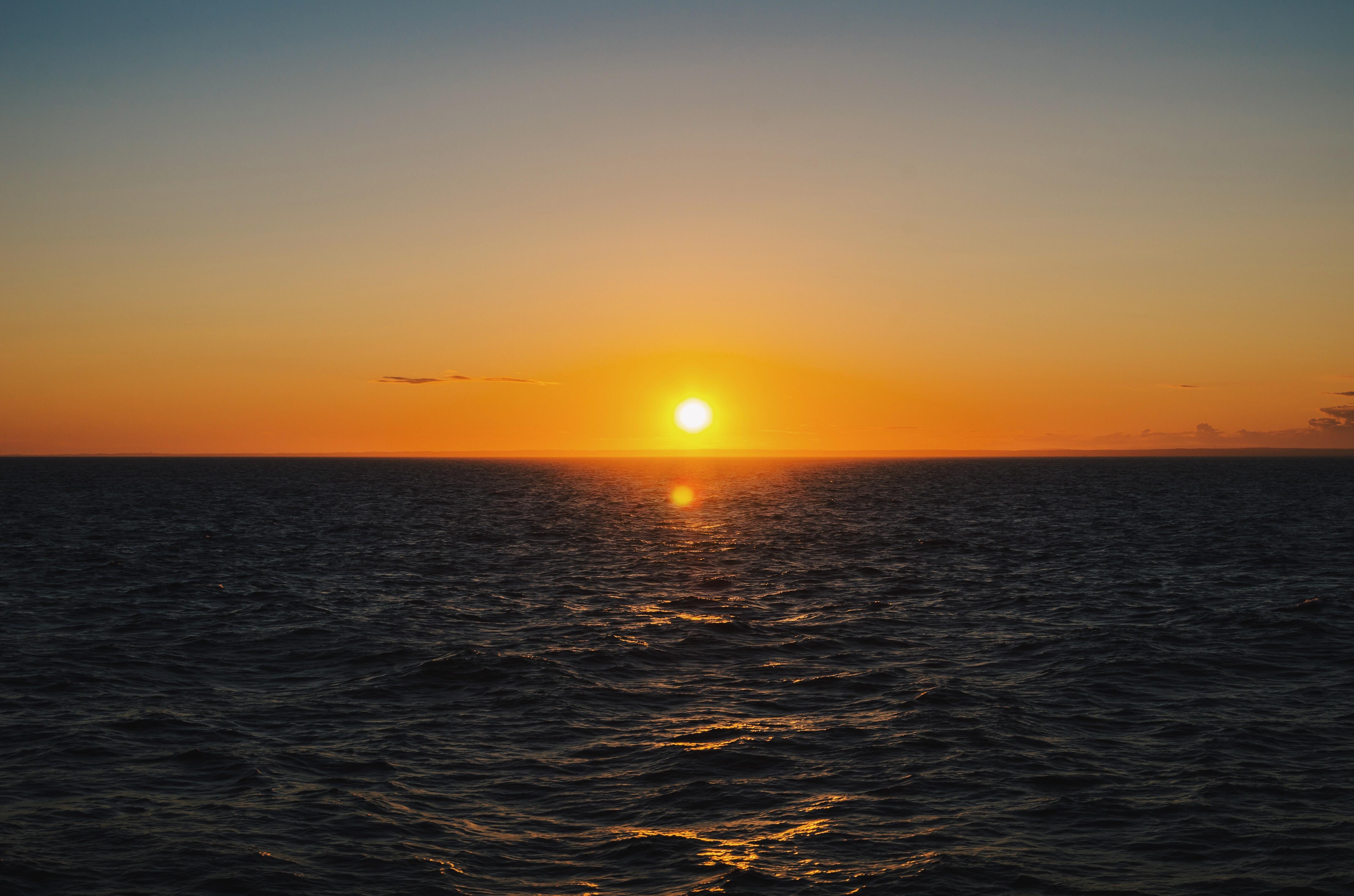 A dark orange sunset over ocean waves at New Shoreham.