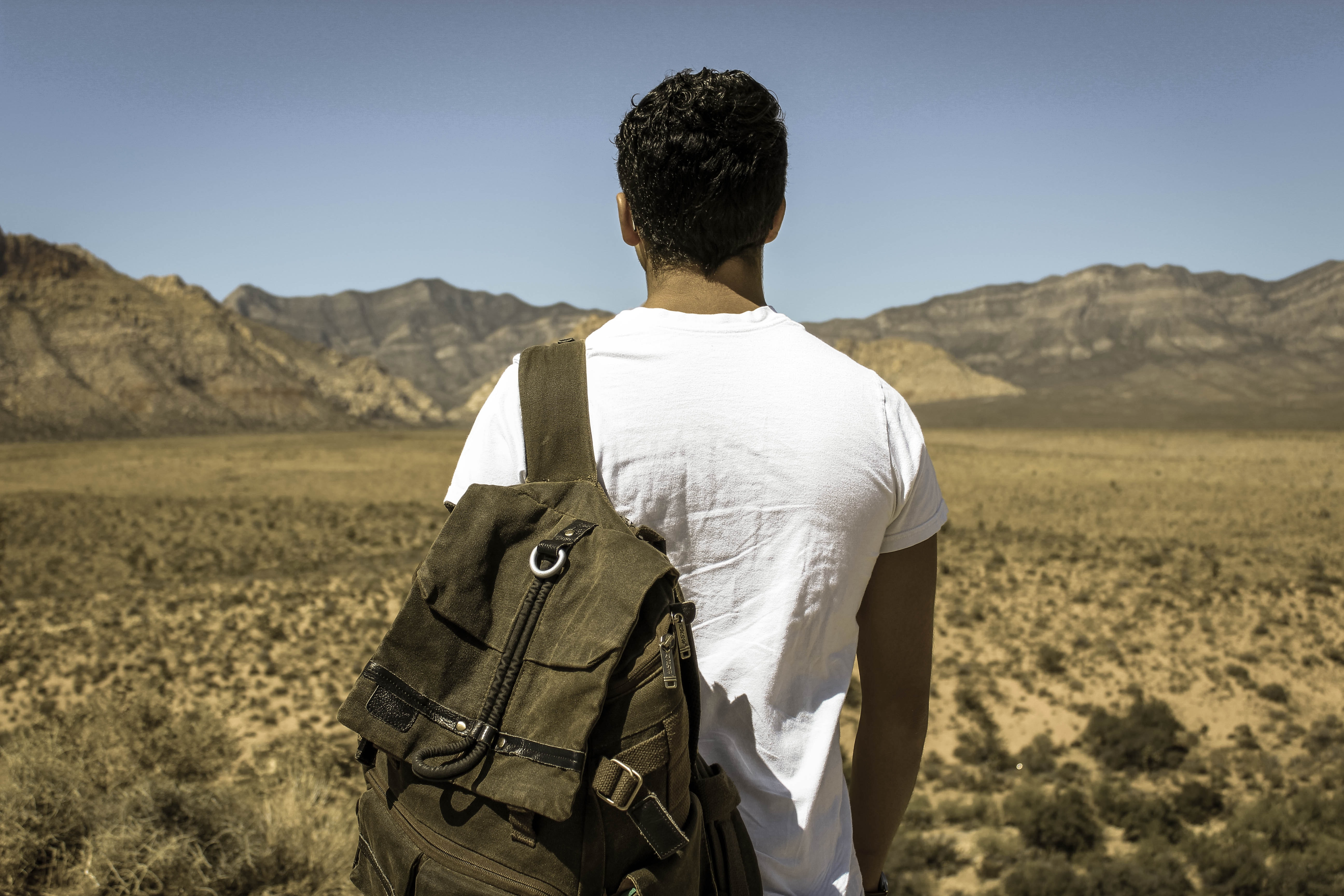 A man with a backpack on his shoulder looking at the semi-arid landscape in front of him