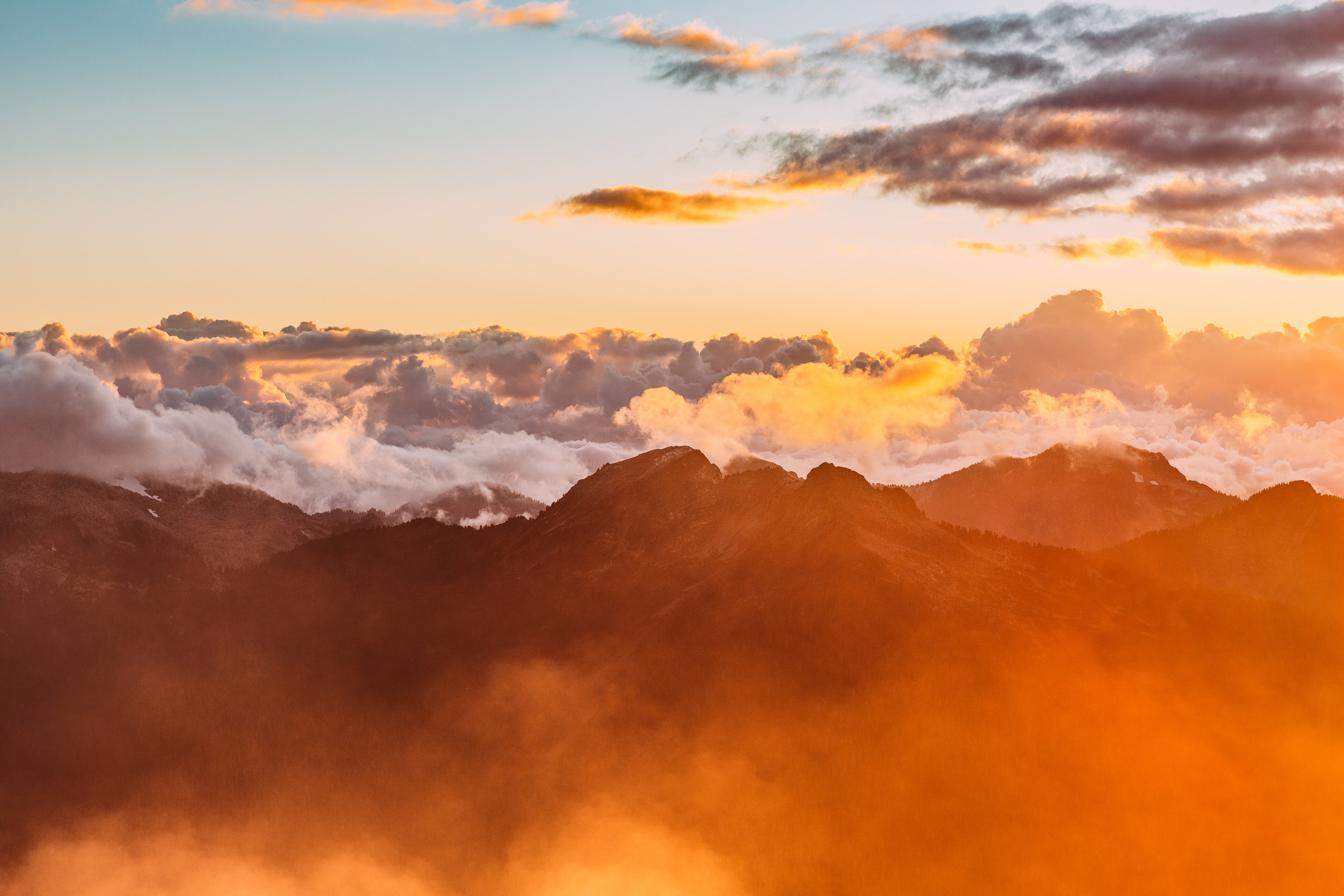 Clouds envelop a mountain range during sunset