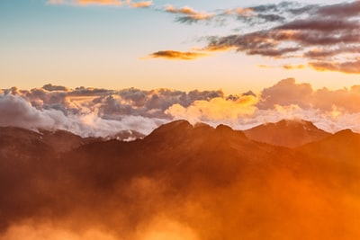 landscape photography of mountains with cloudy skies during golden hour orange teams background