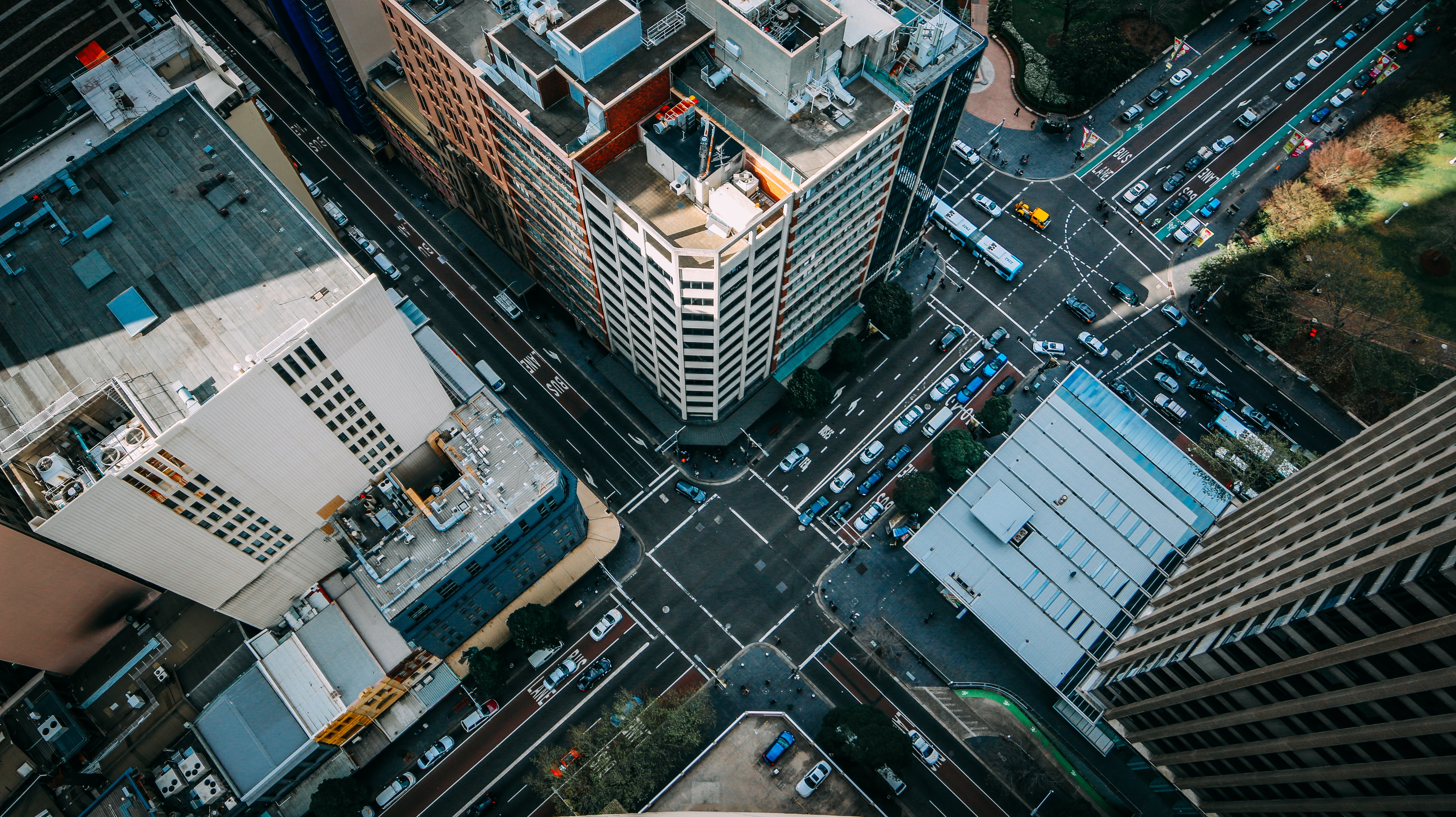 Drone shot of urban traffic crossroads and skyscraper rooftops daytime