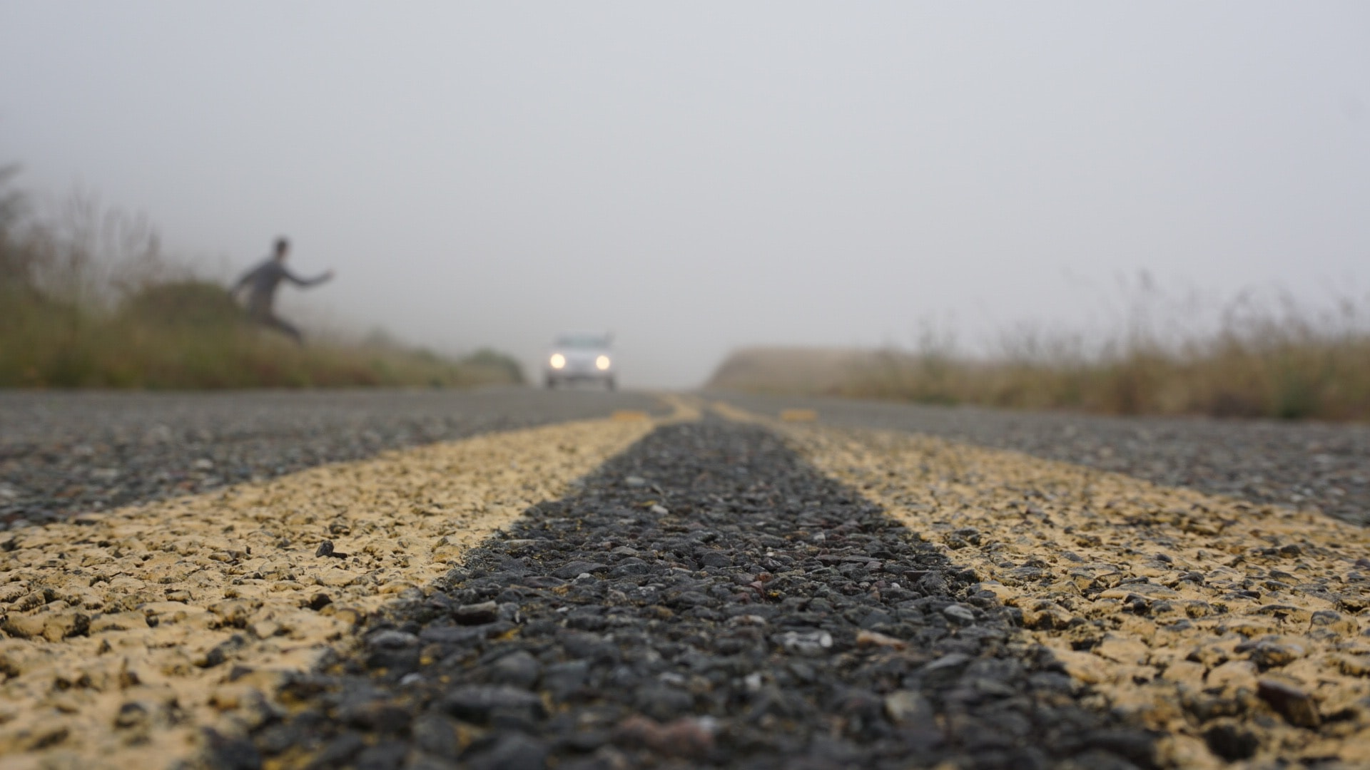 Road level view of a person crossing the foggy road.