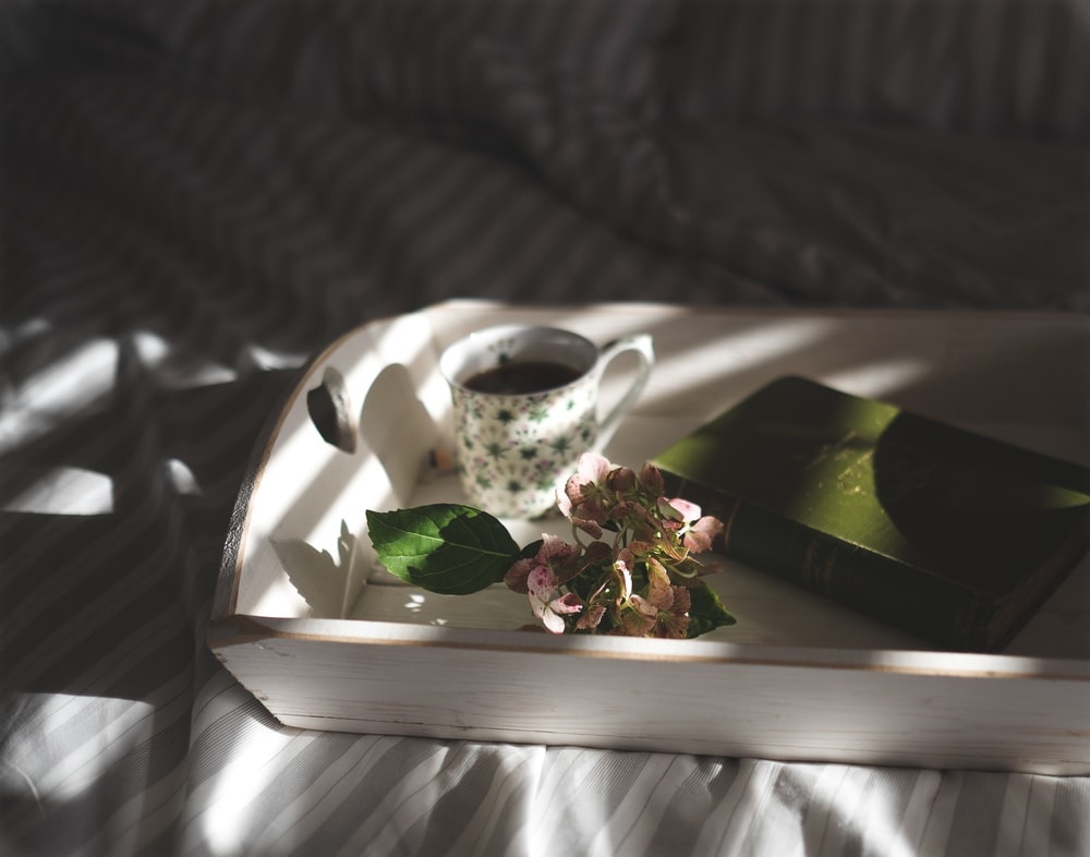 teacup beside pink flowers on tray