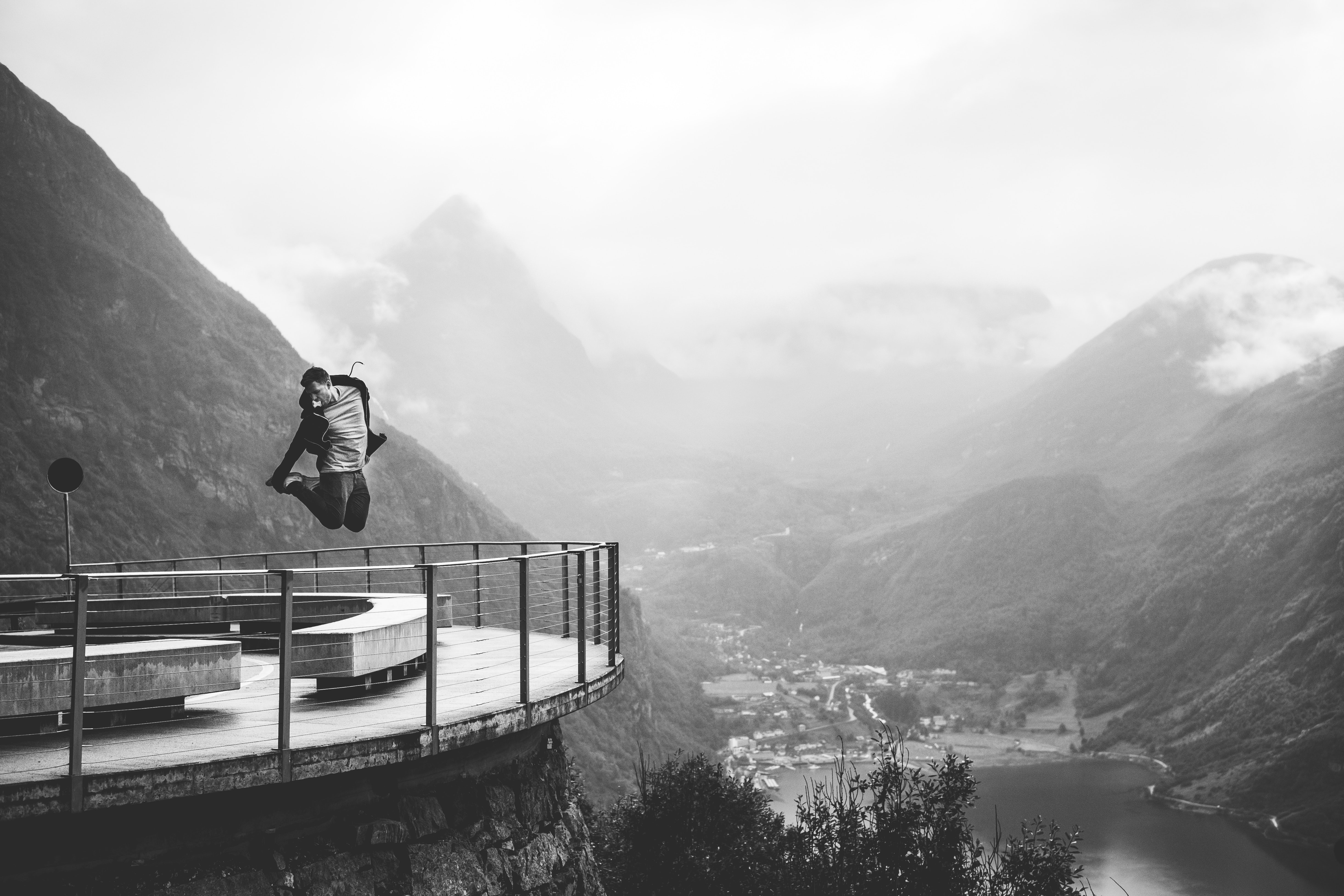 A black and white shot of a man jumping above a rail of an observation platform in a mountainous landscape