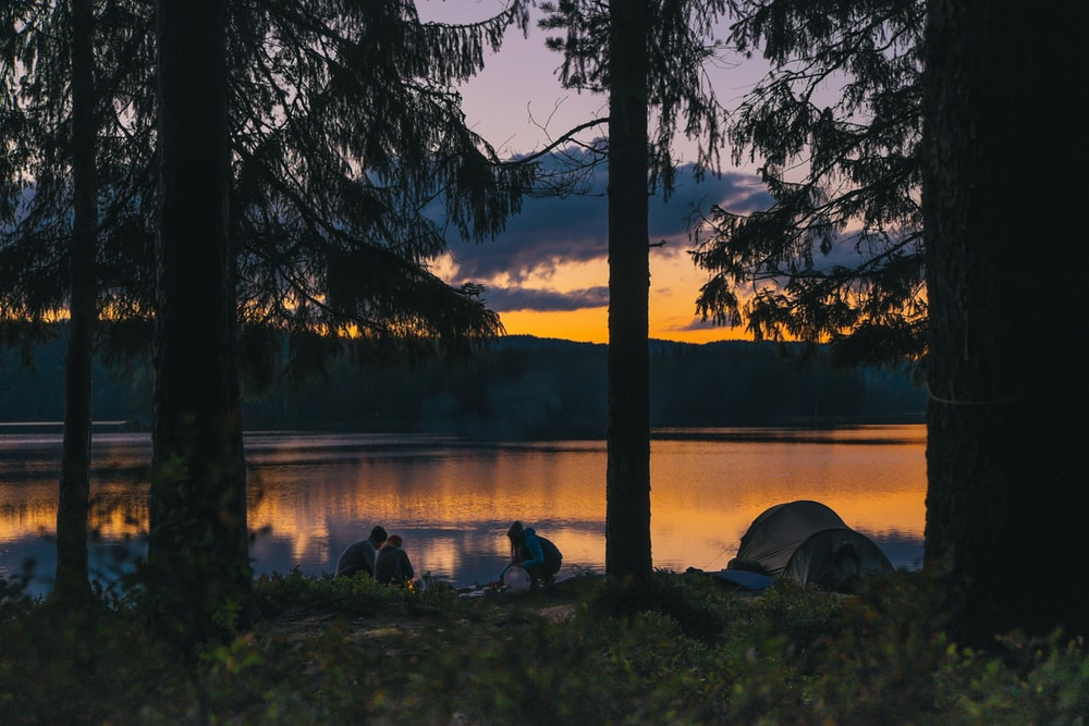 People camping with a gold sunset through forest trees at a tranquil lake that reflects the warm light.