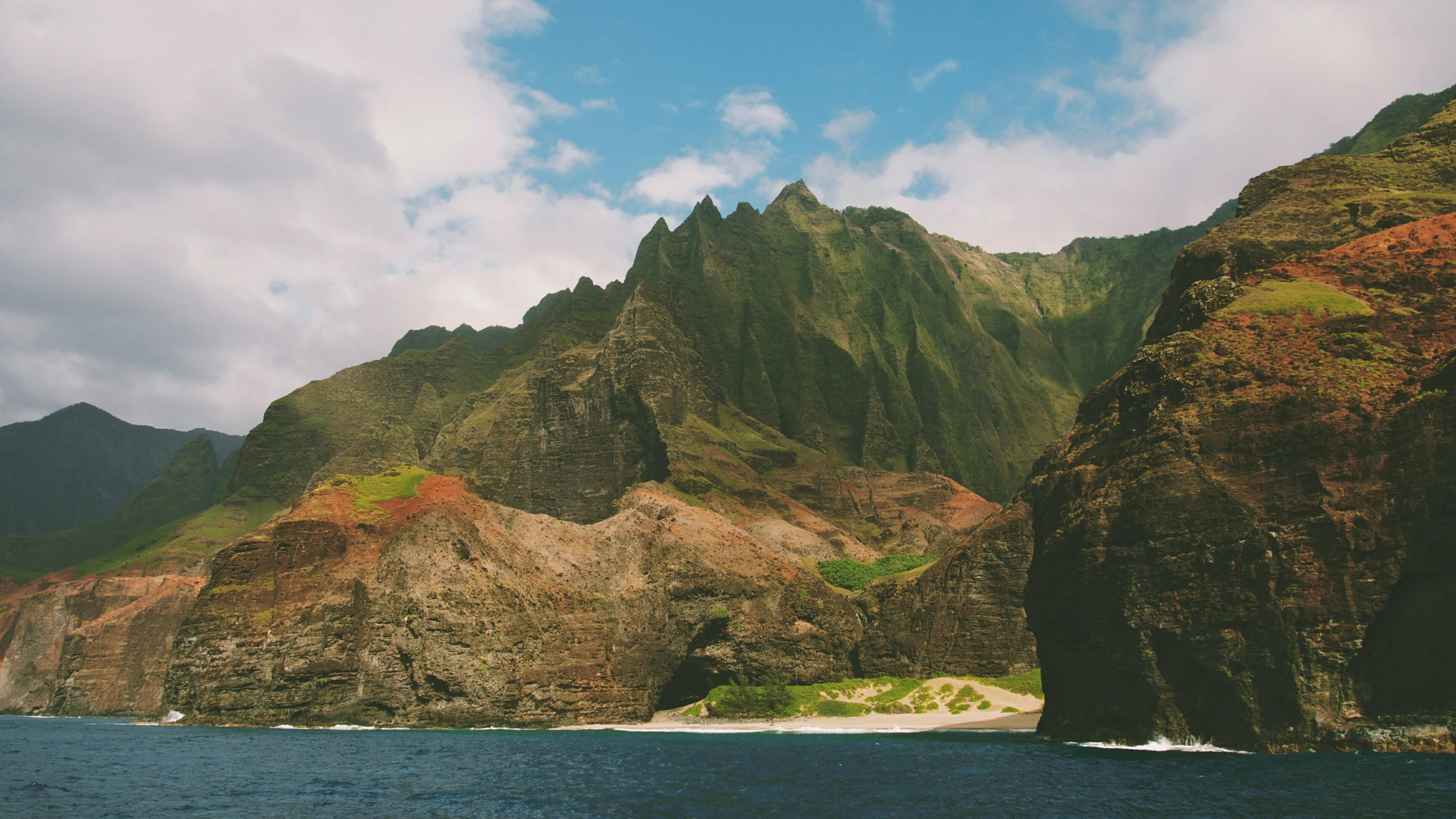 Scenic view of humongous mountain and beach just off the coast of the ocean