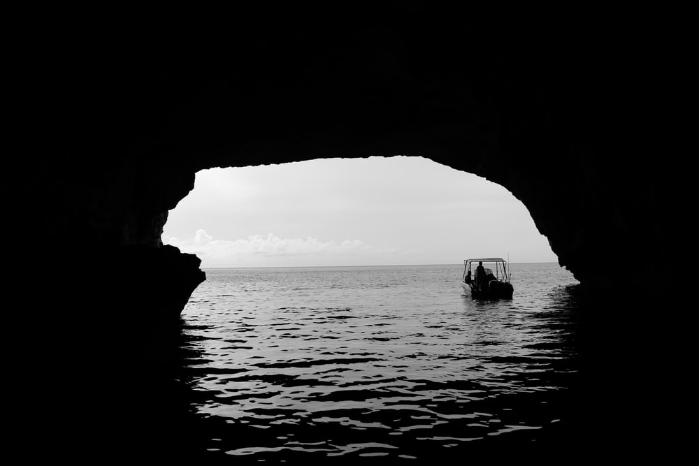 boat on body of water outside the cave