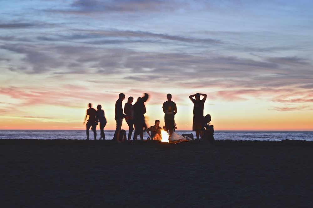 group of people setting up campfire