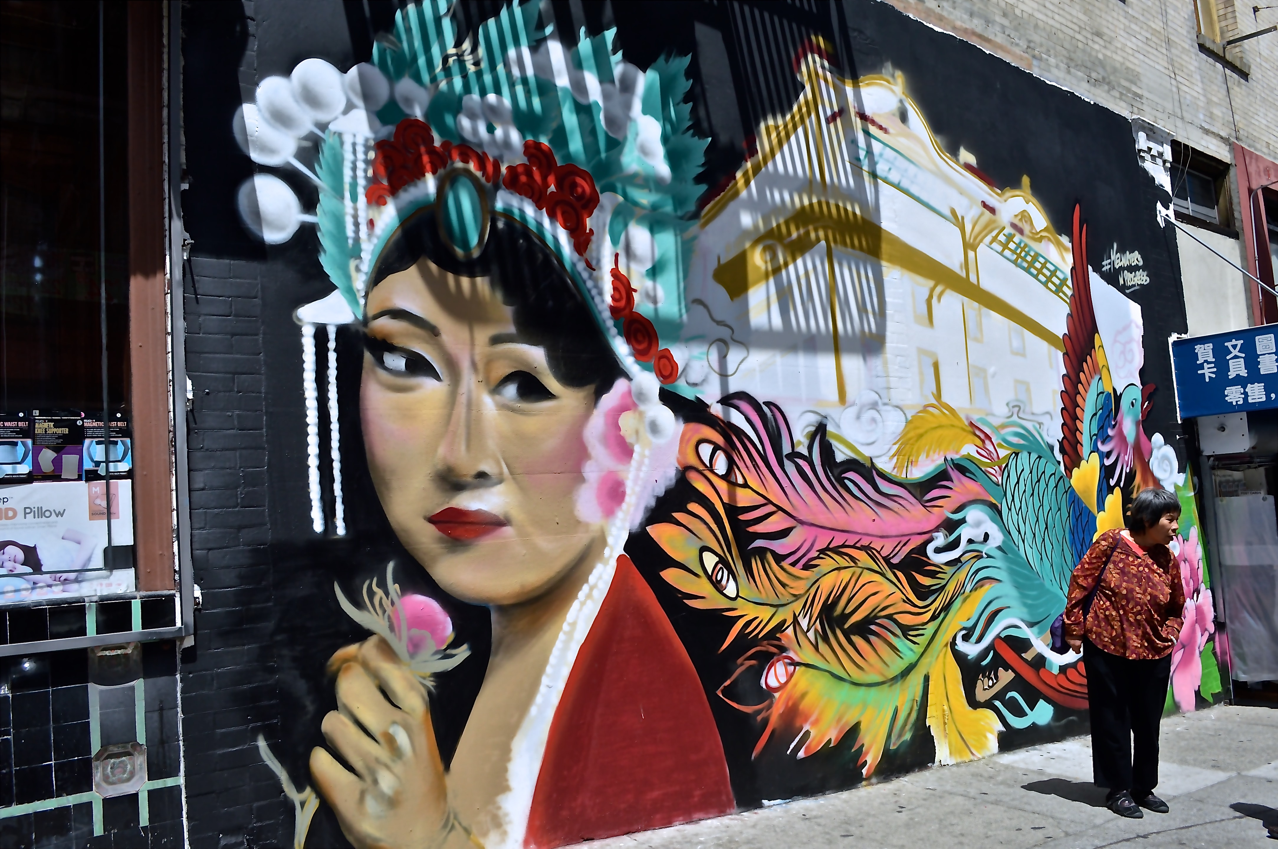 An Asian woman holding a flower, painted on a wall.