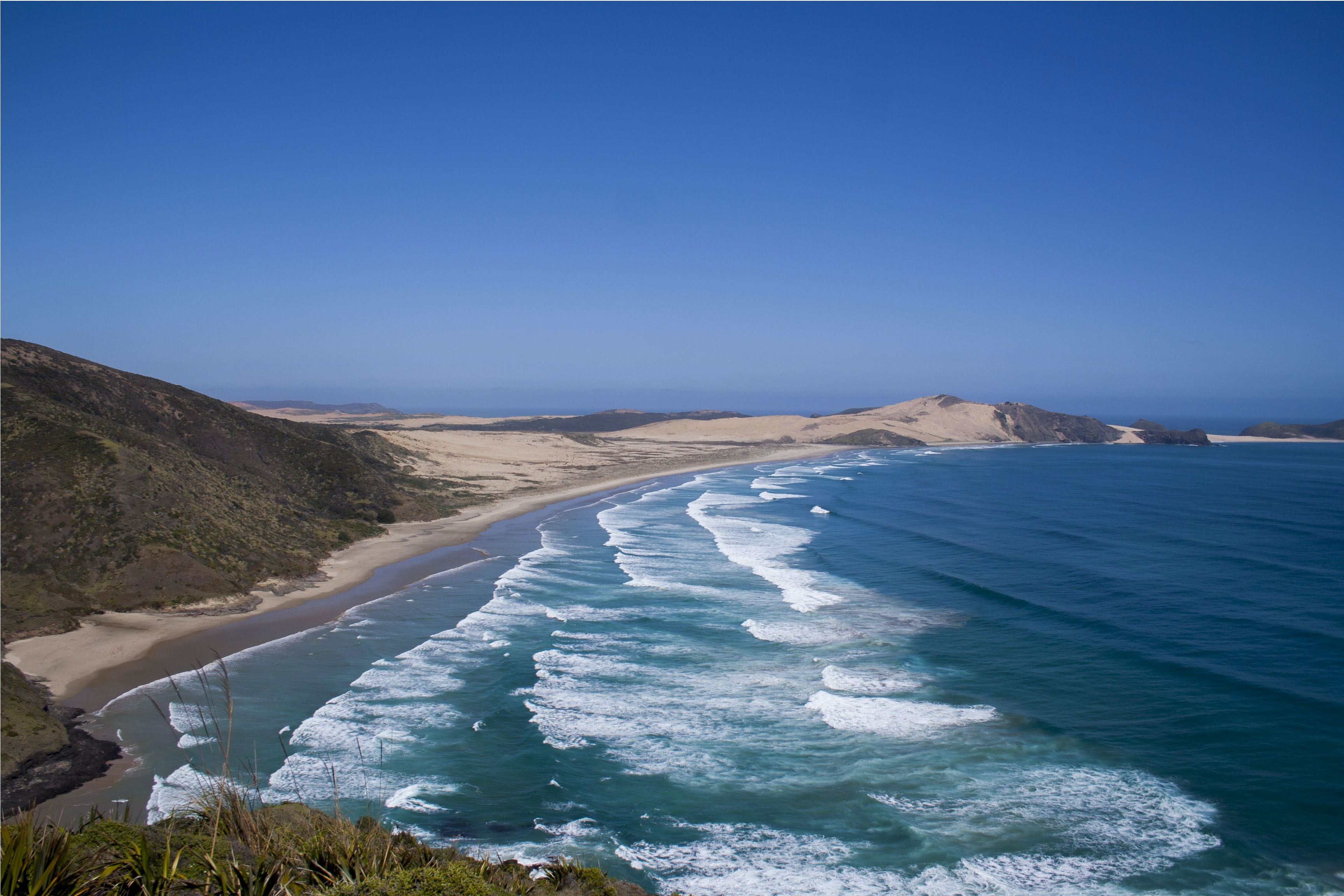 Ocean washing on the hilly sand shore at Cape Reinga