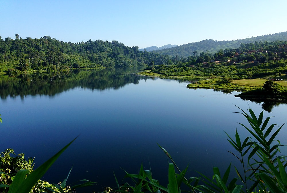 calm body of water near green trees and mountain at daytime