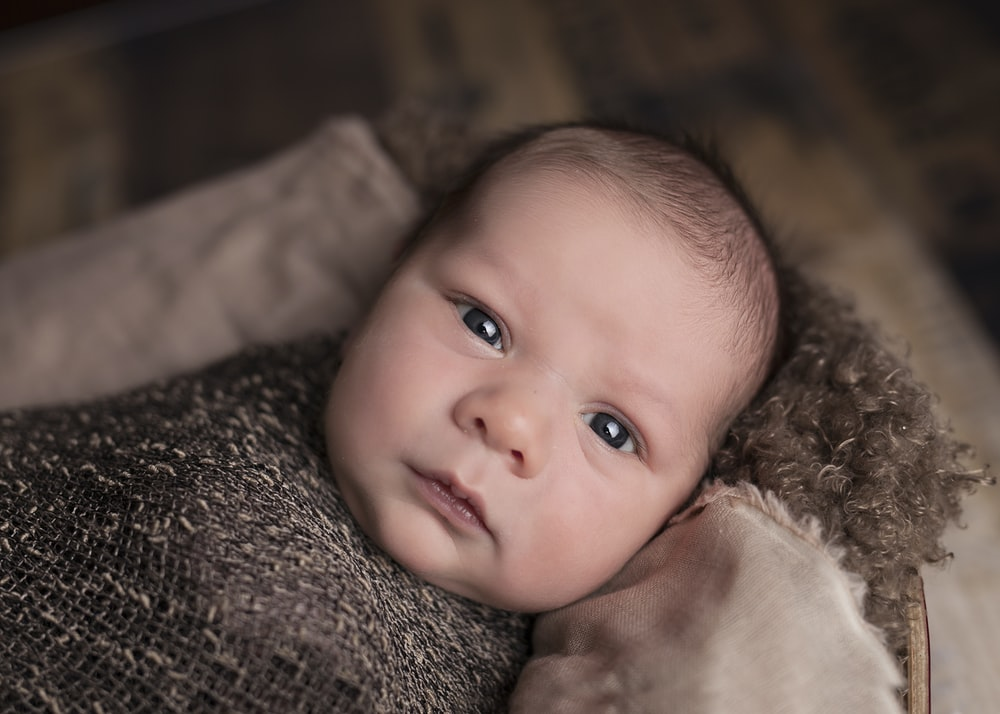 baby in brown swaddle