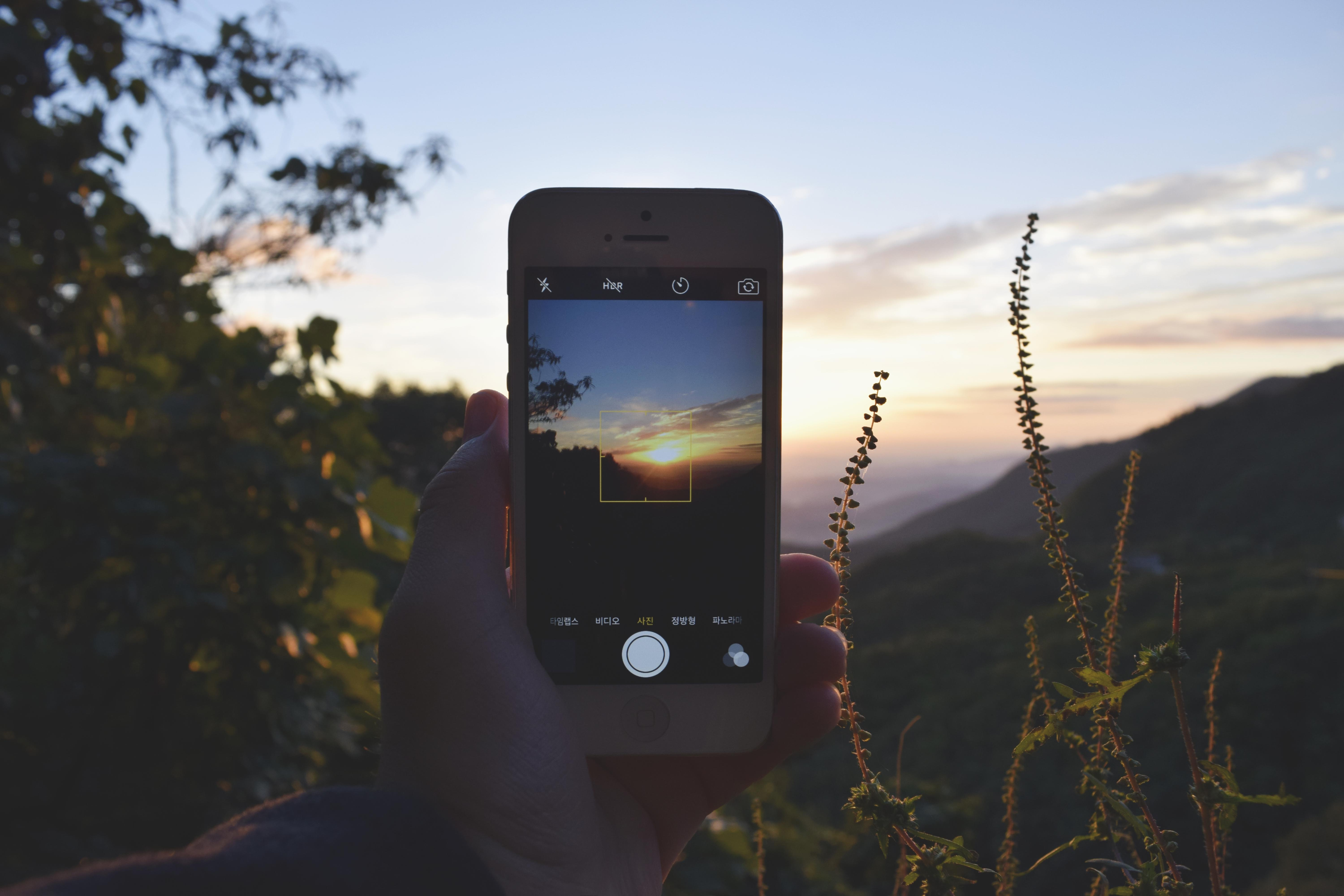 A sunset is taken through the camera of an iPhone as a snapshot against foliage and mountains.