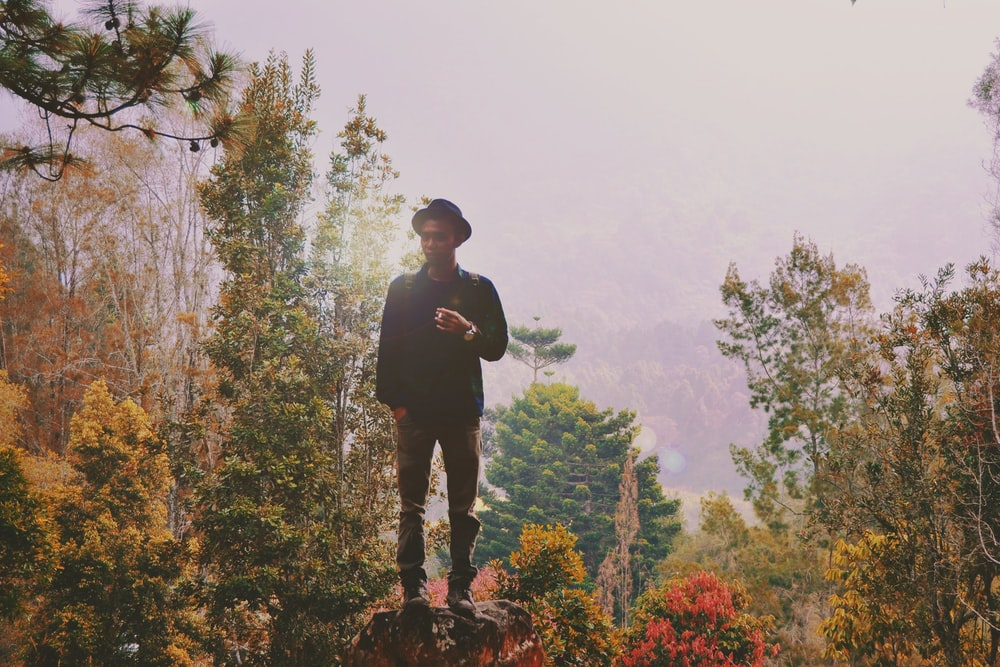 A man dressed in a hipster hat standing on a boulder in fall