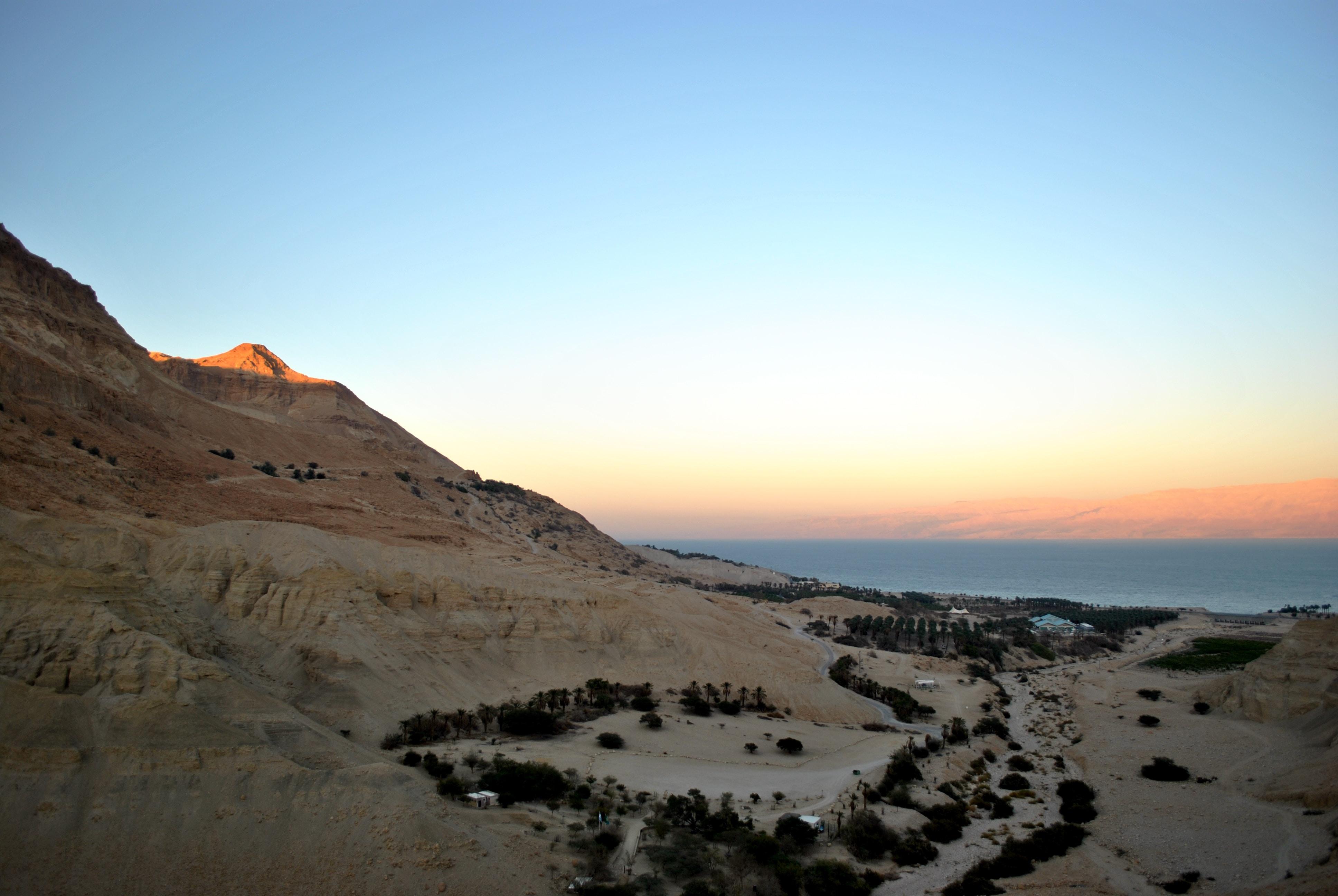 Sun peaks over the horizon over the desert terrain