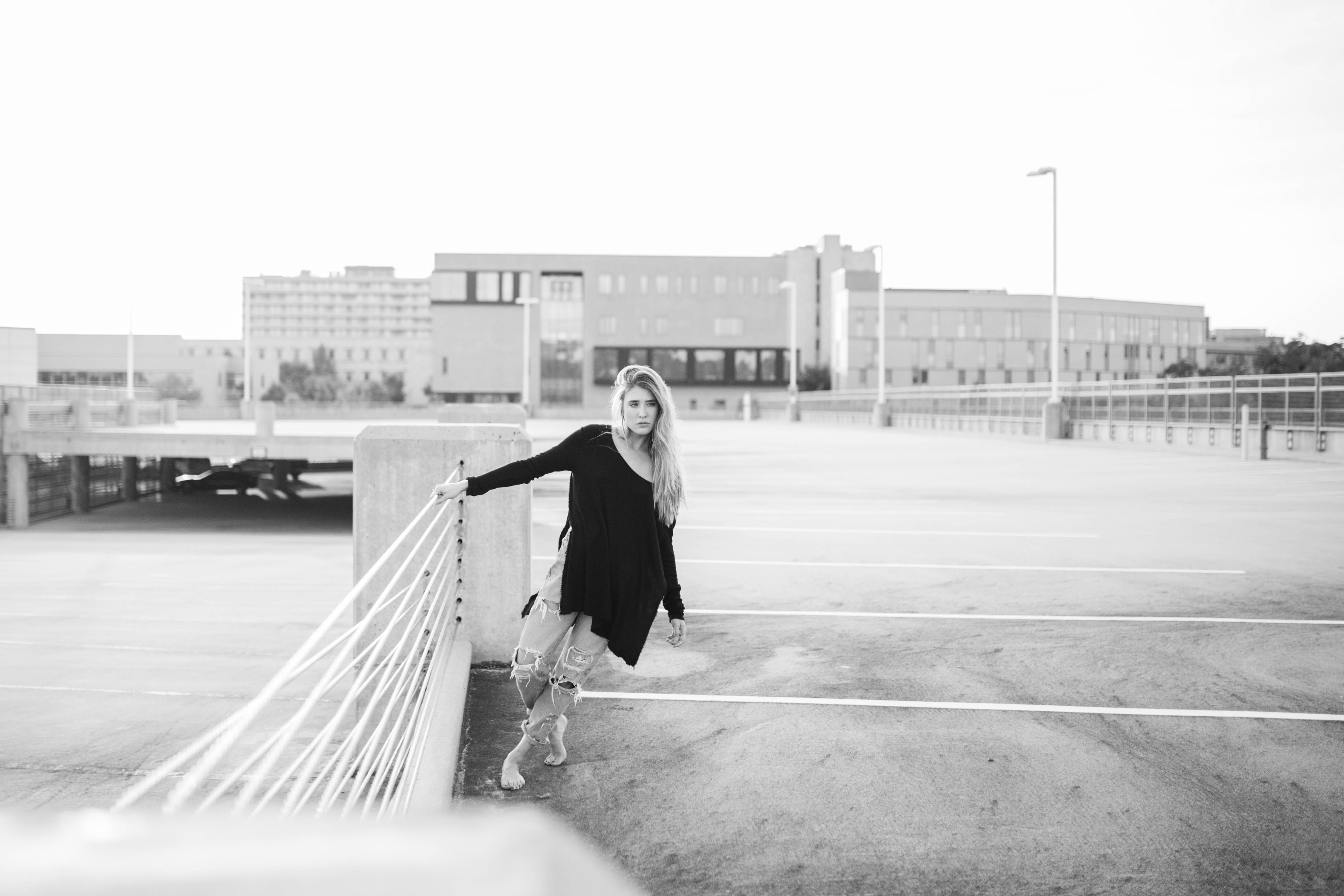 Black and white shot of attractive blonde woman posing in car park University of Arkansas