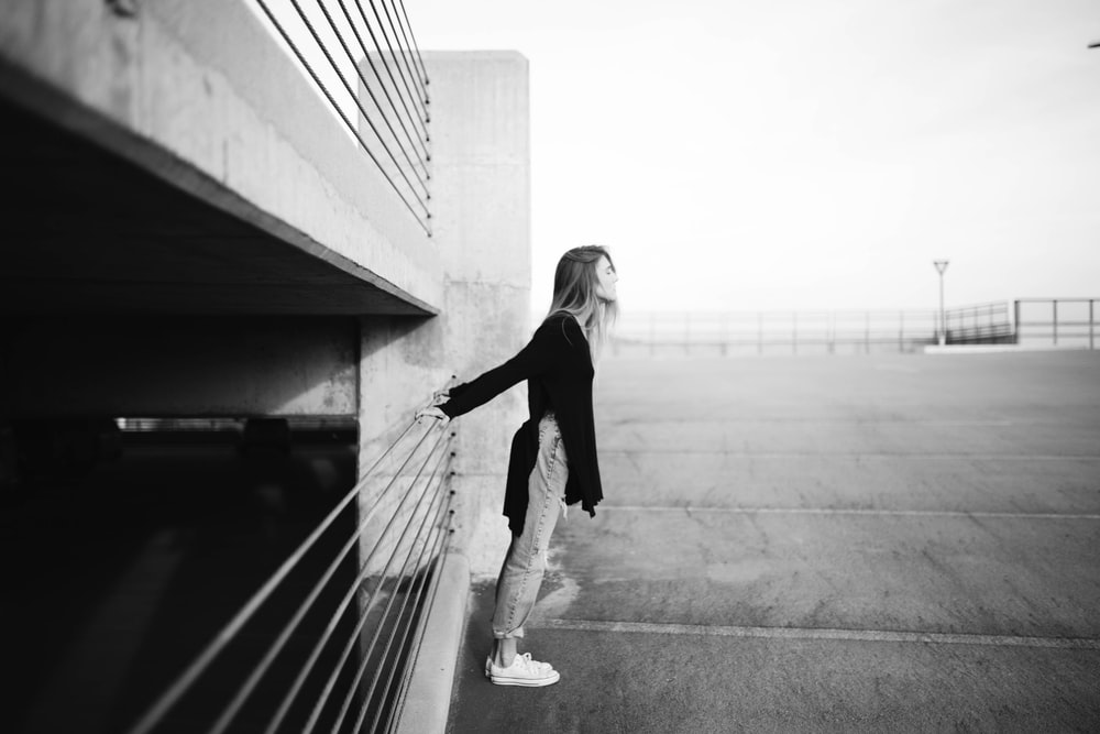 grayscale photography of woman standing near building