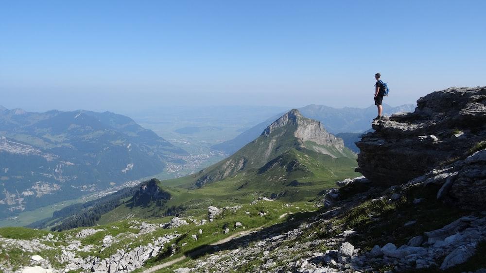 man standing near cliff facing mountains