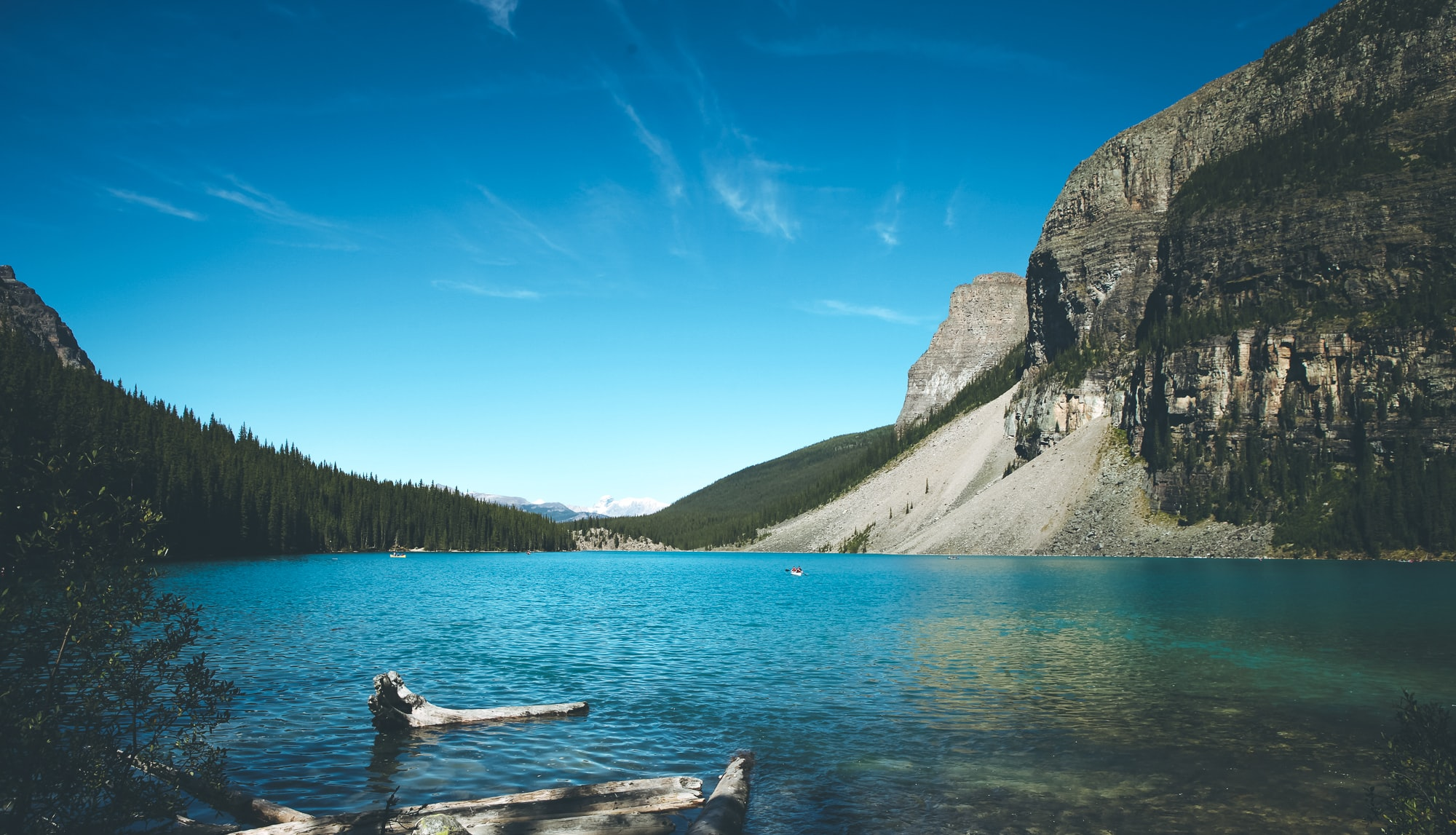 body of water beside mountain at daytime