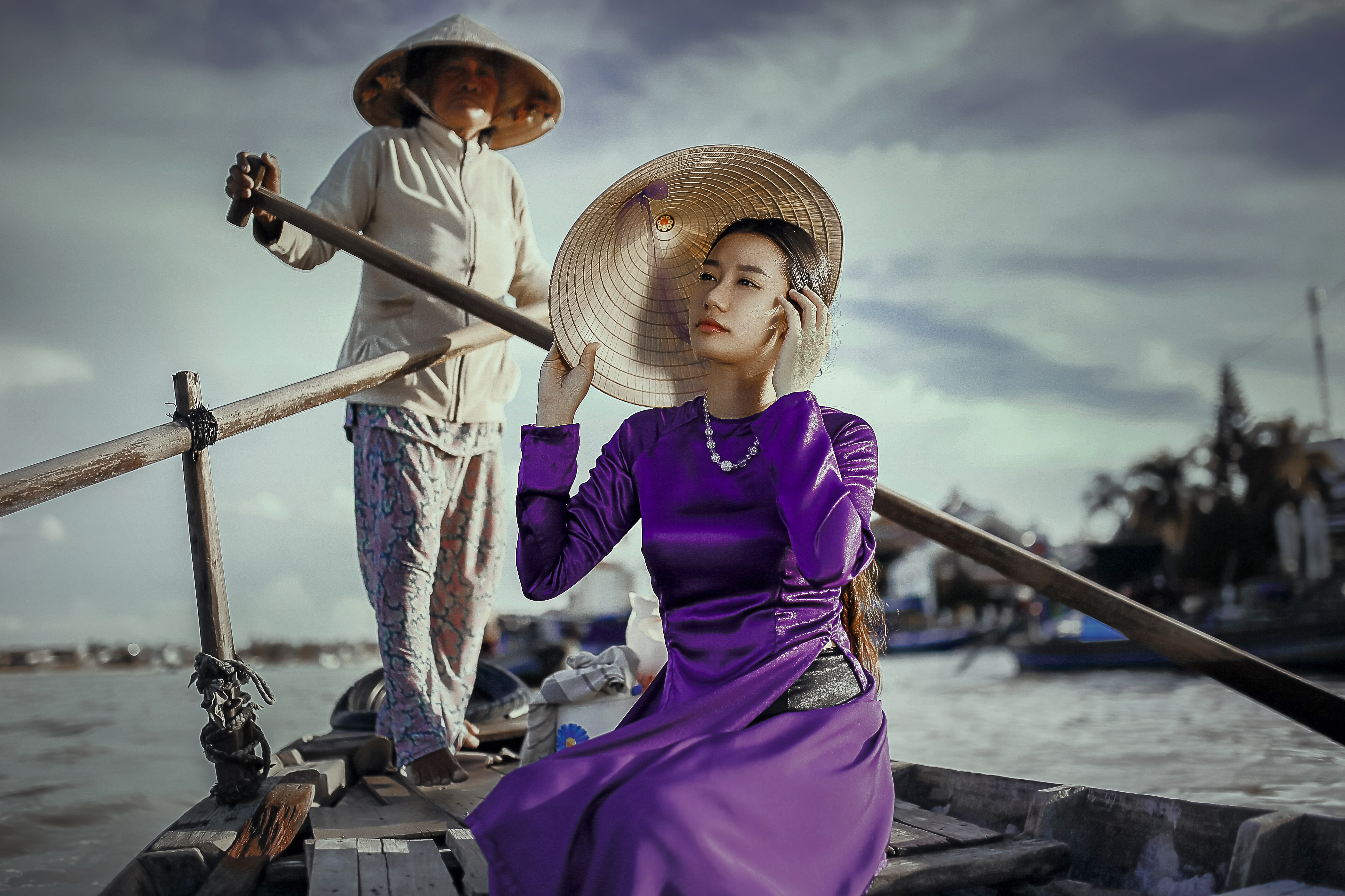 A young Asian woman in a purple dress and a rice hat on a boat with an elderly woman at the back