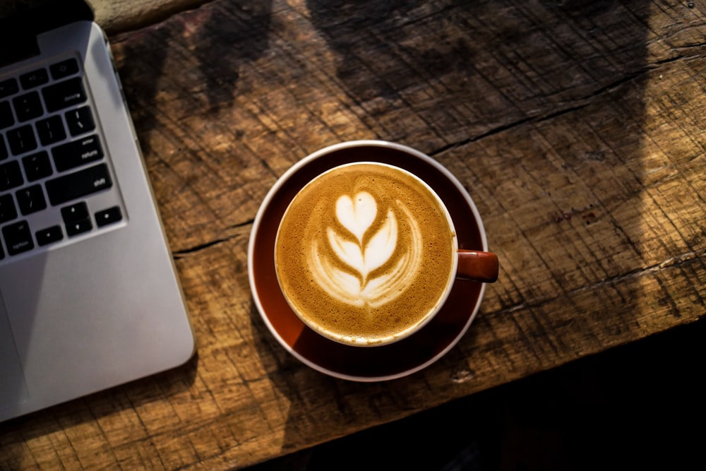 caffe latte on white ceramic cup beside silver and black laptop computer