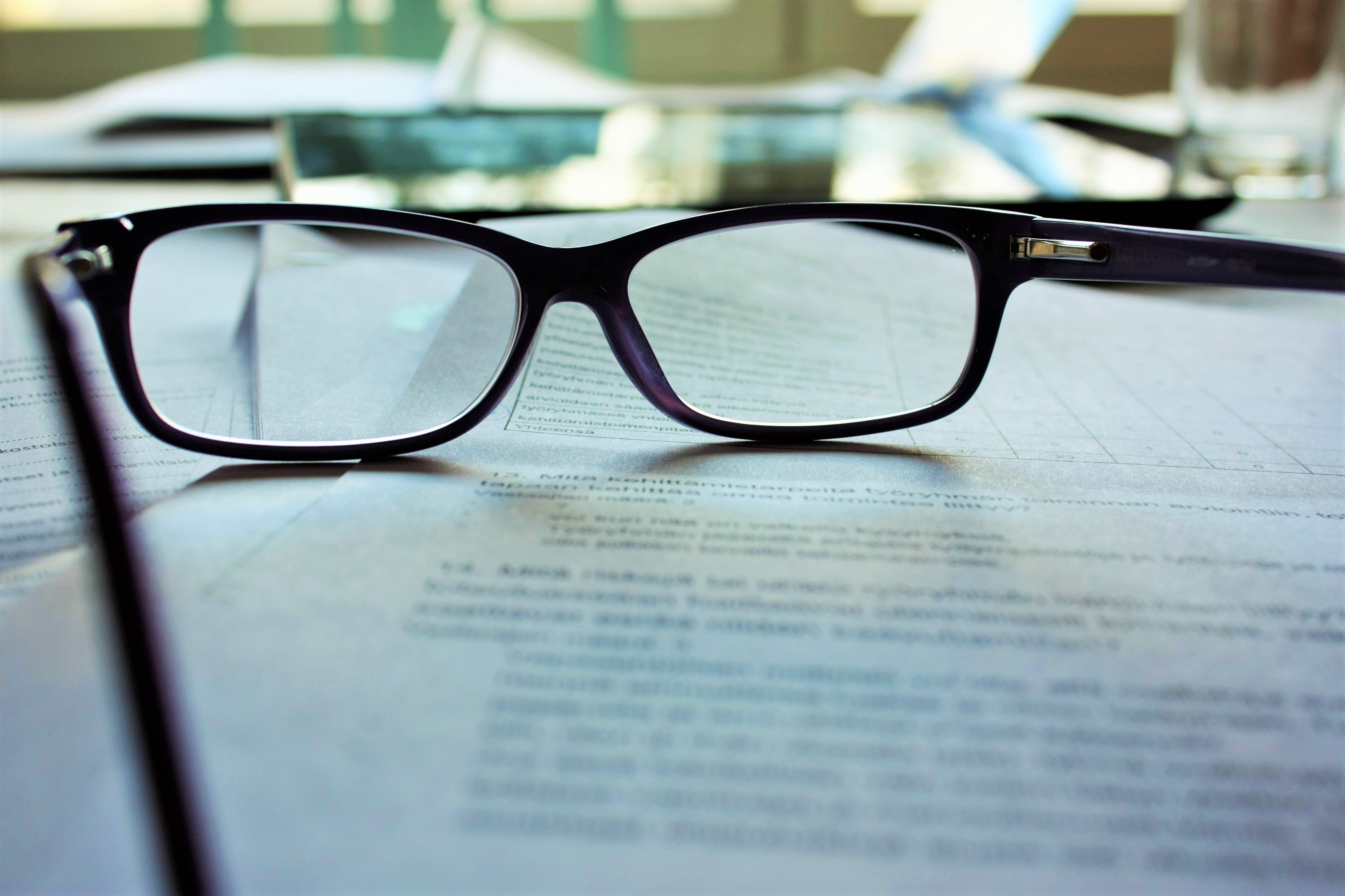 Close-up of a pair of glasses on printouts