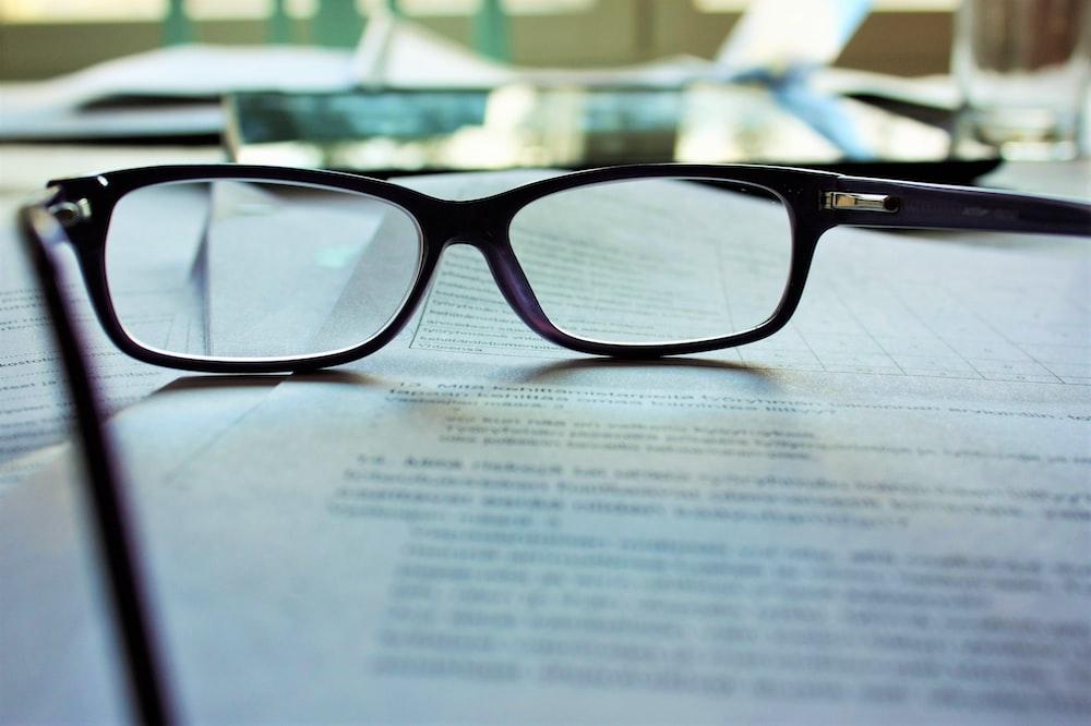 black-framed eyeglasses on white printing paper