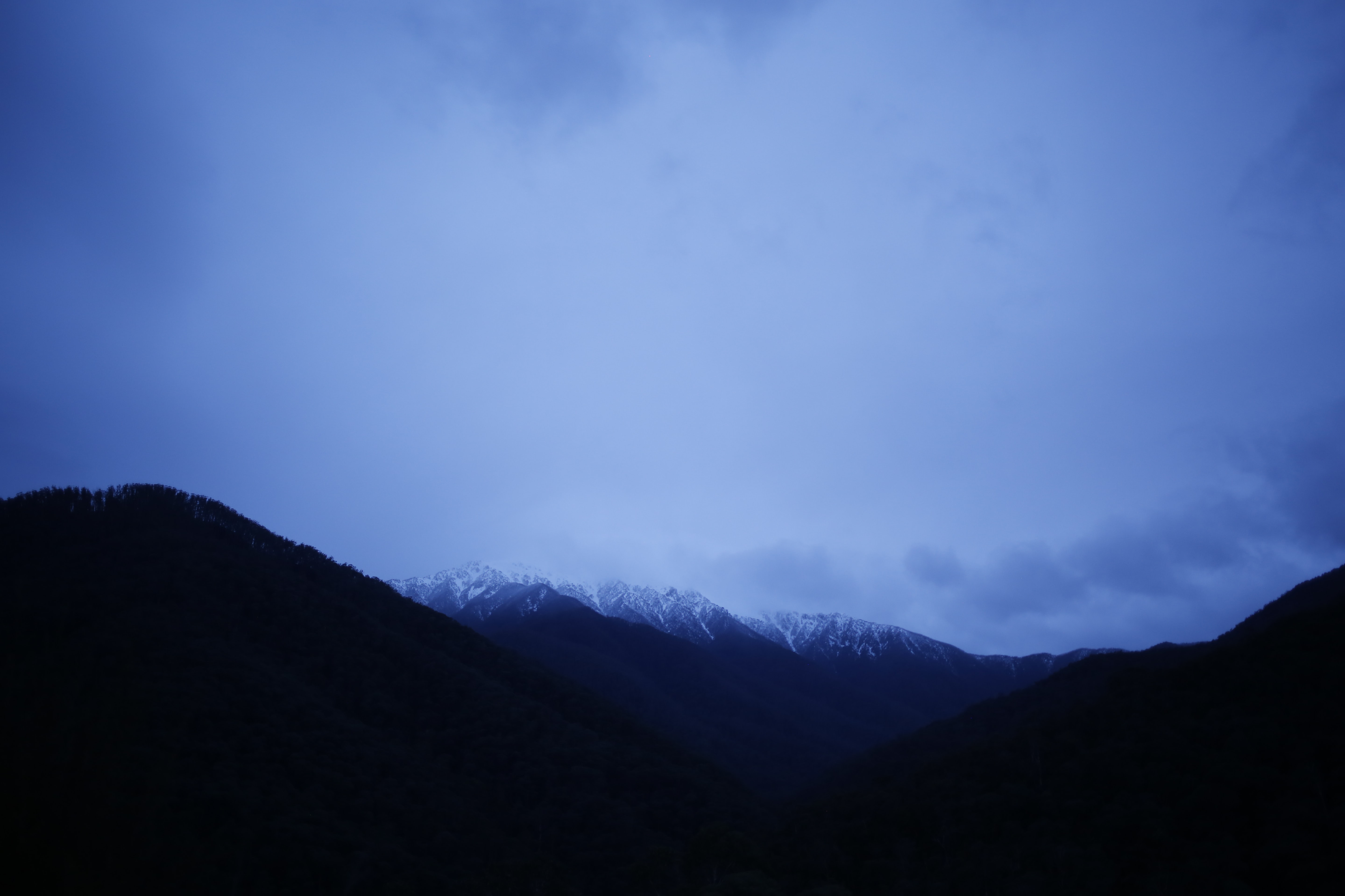 Cloudy blue sky shines on a silhouette of mountains in Falls Creek