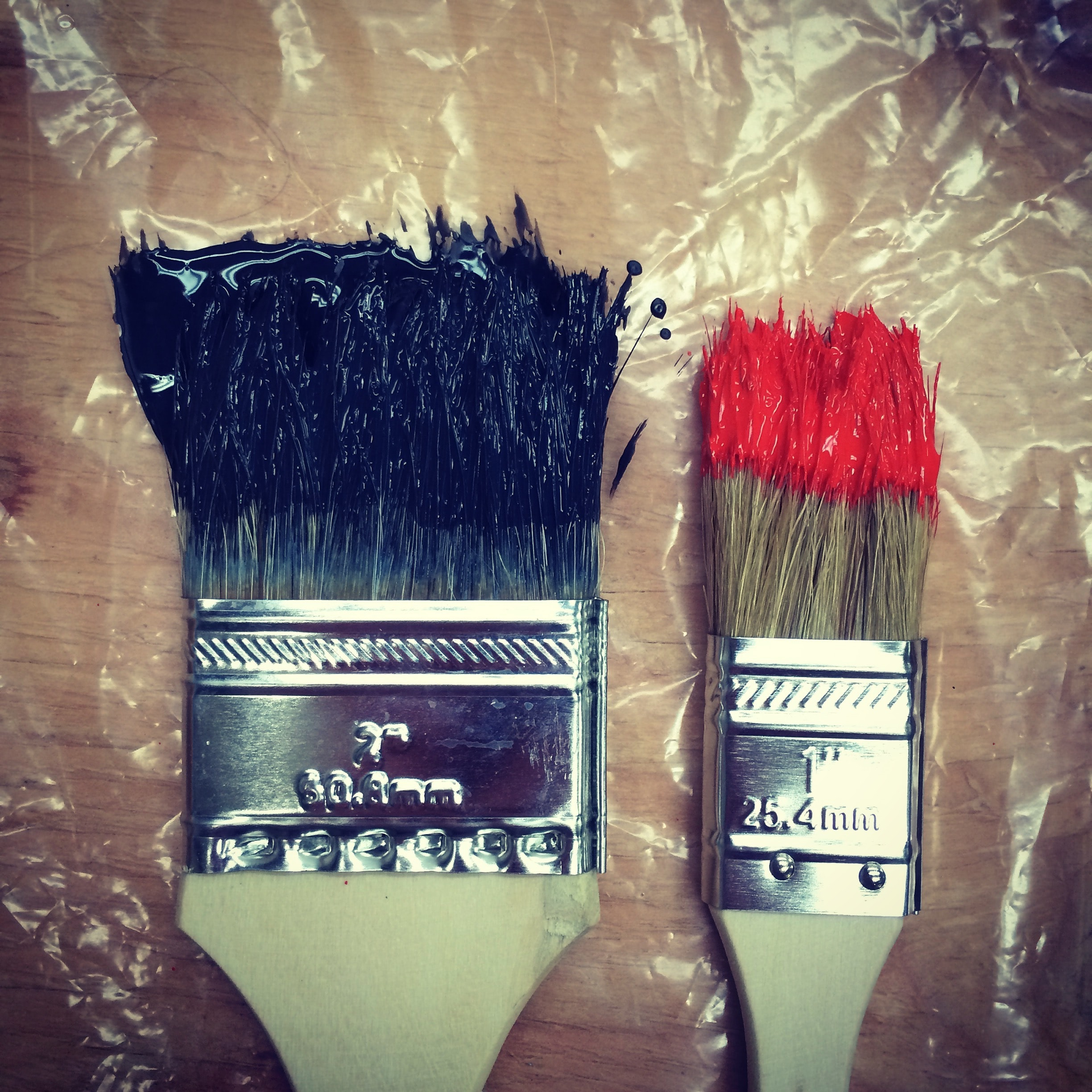 Two paintbrushes of varying size dipped in paint lying on table, California College of the Arts