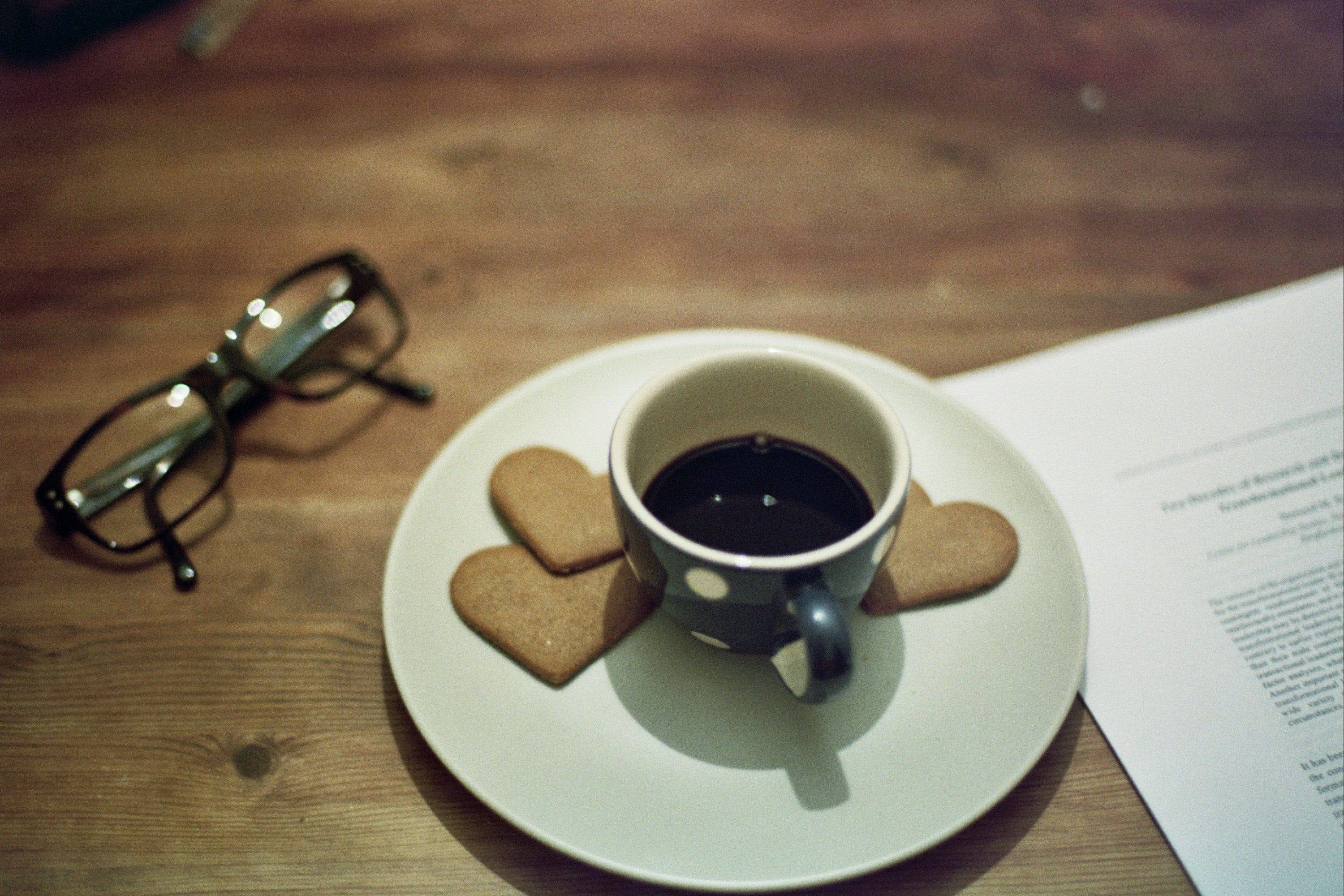 Tiny polka-dot mug filled with coffee on a saucer with heart biscuits and a pair of glasses on the table