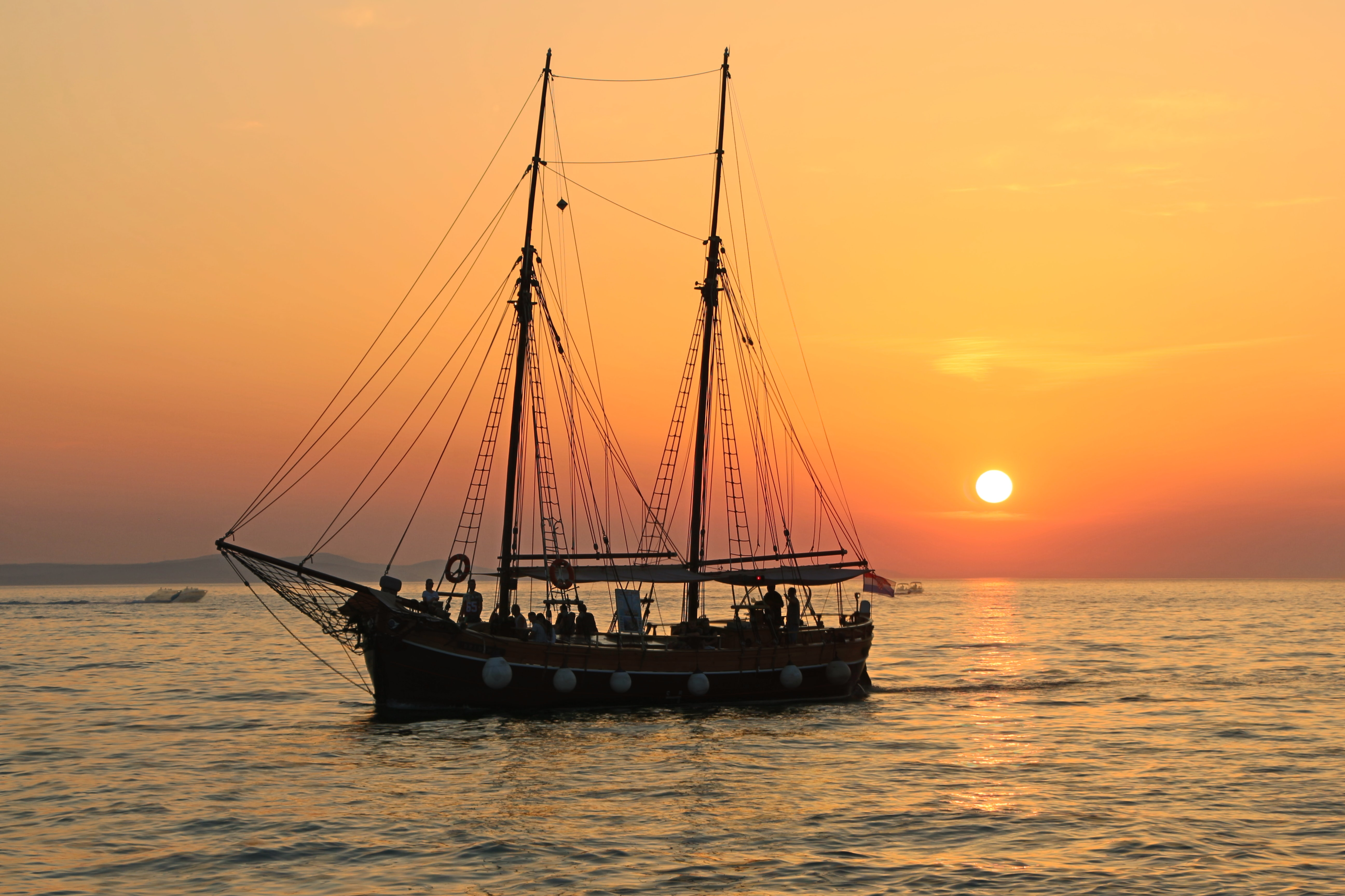 A sailboat on a tranquil sea as the sun sets in the distance