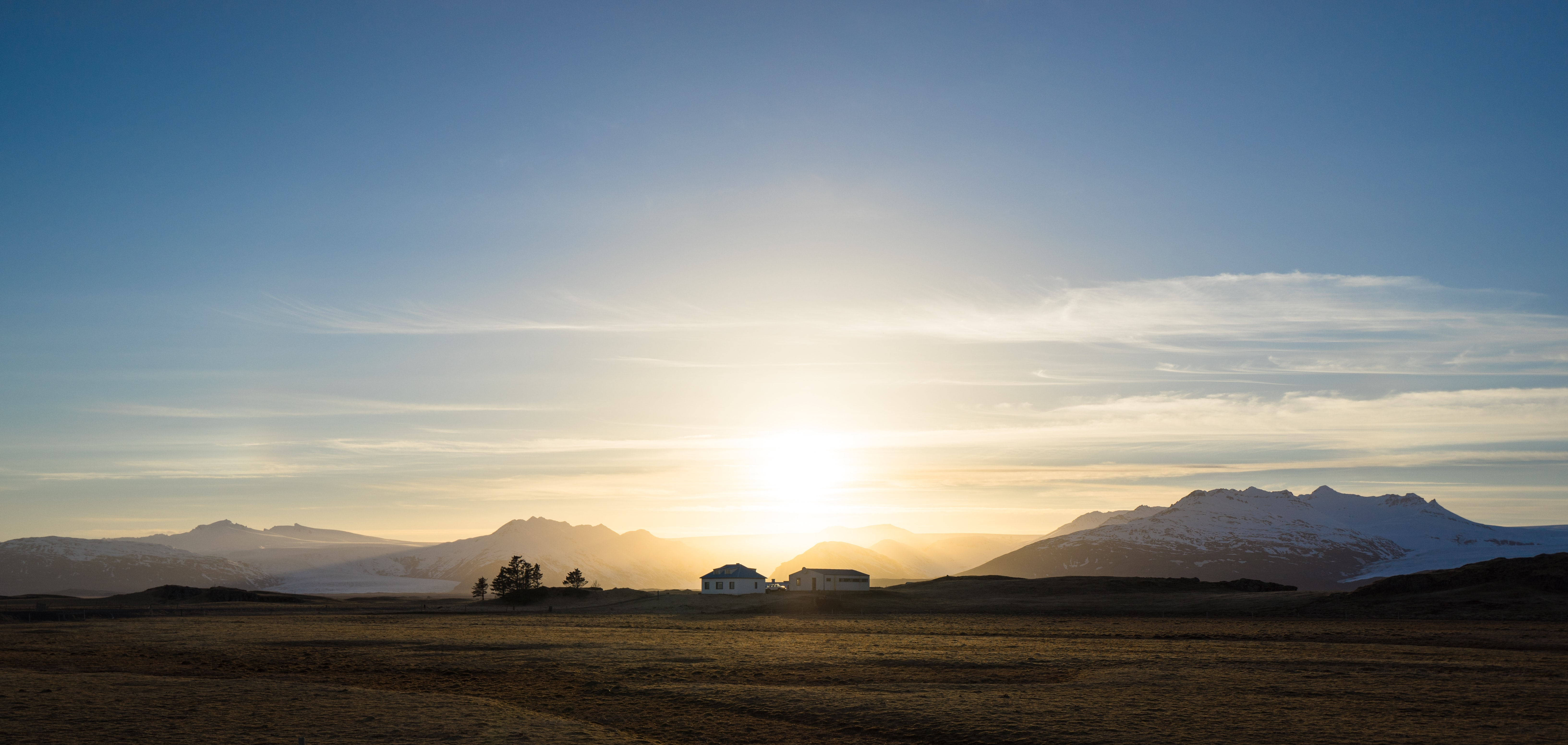 A sunset silhouette of a mountain house in a meadow, in front of the mountains in Iceland