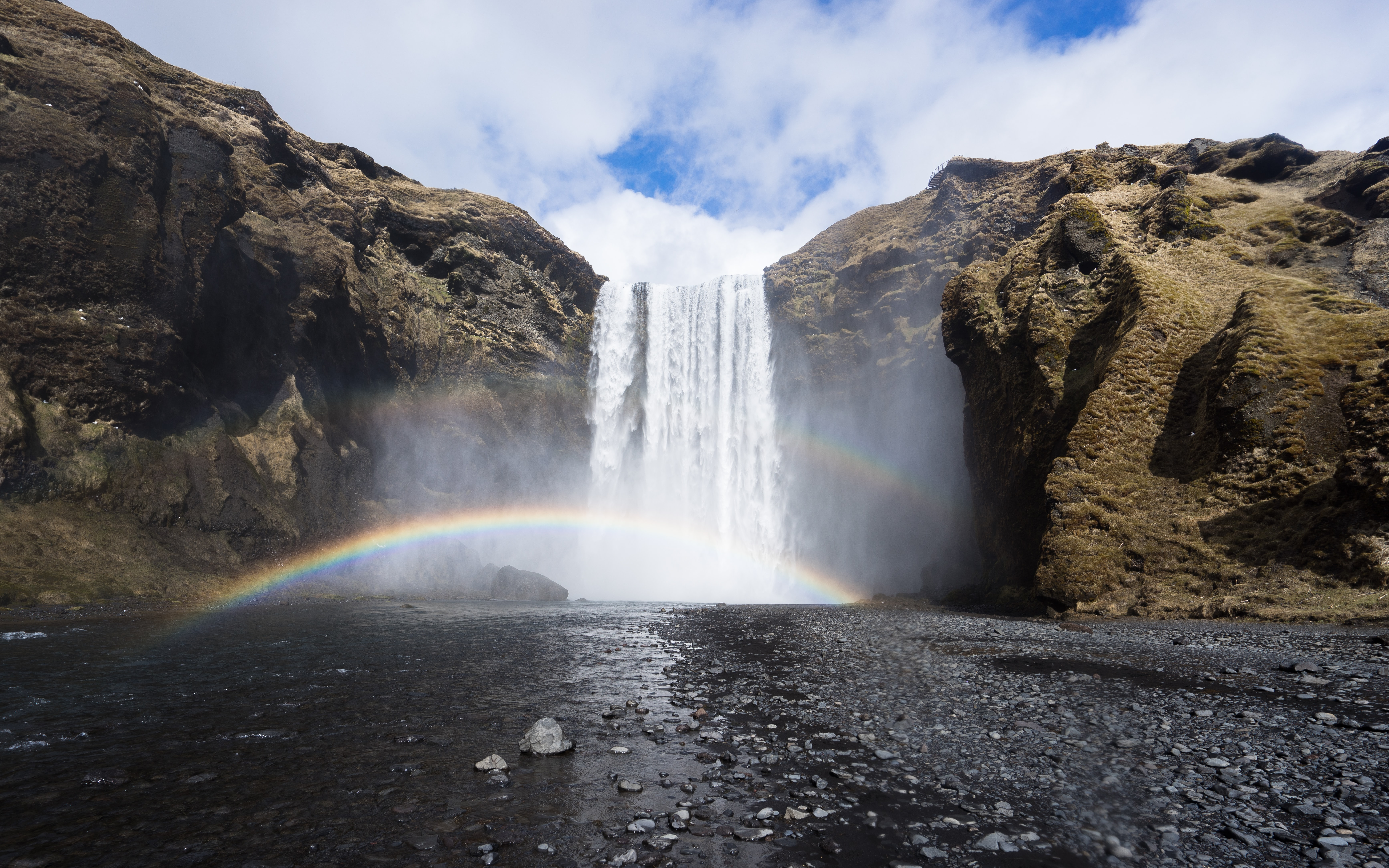 A magnificent shot of a waterfall tumbling down from a rock with a small rainbow in the spraying water