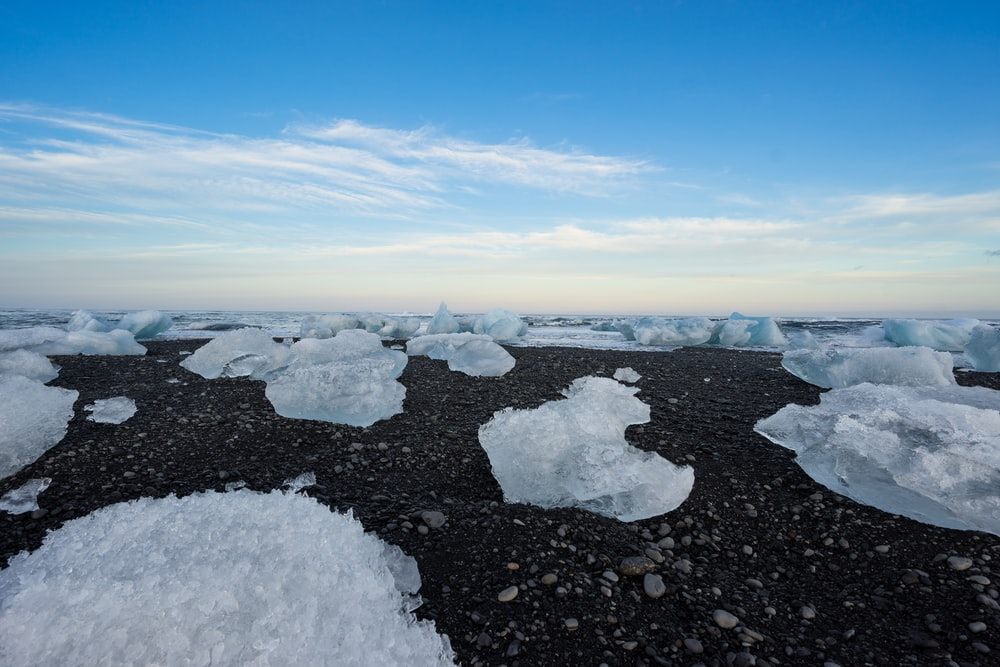 ice on black rocks under white clouds and blue sky