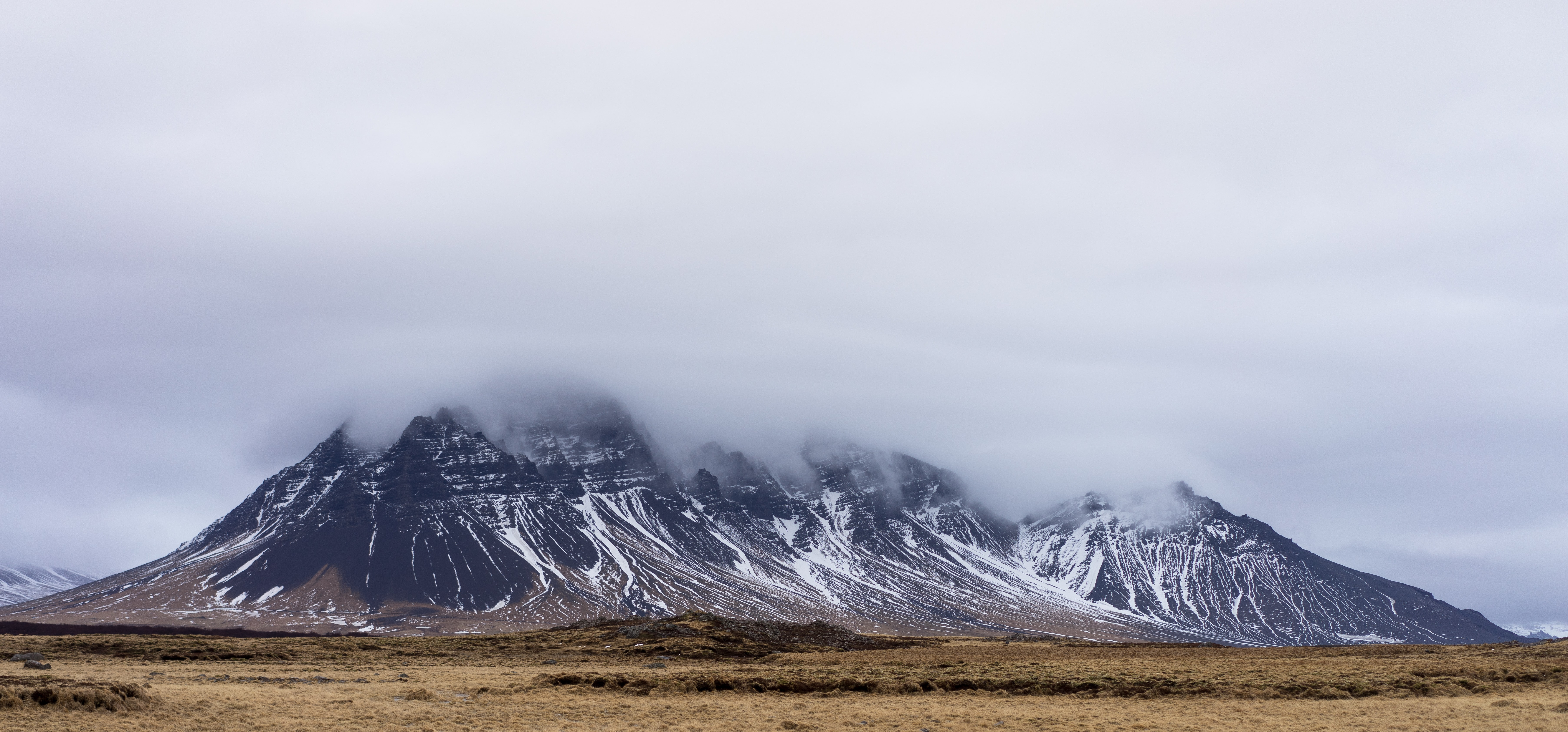 A dark granite mountain shrouded in dense mist