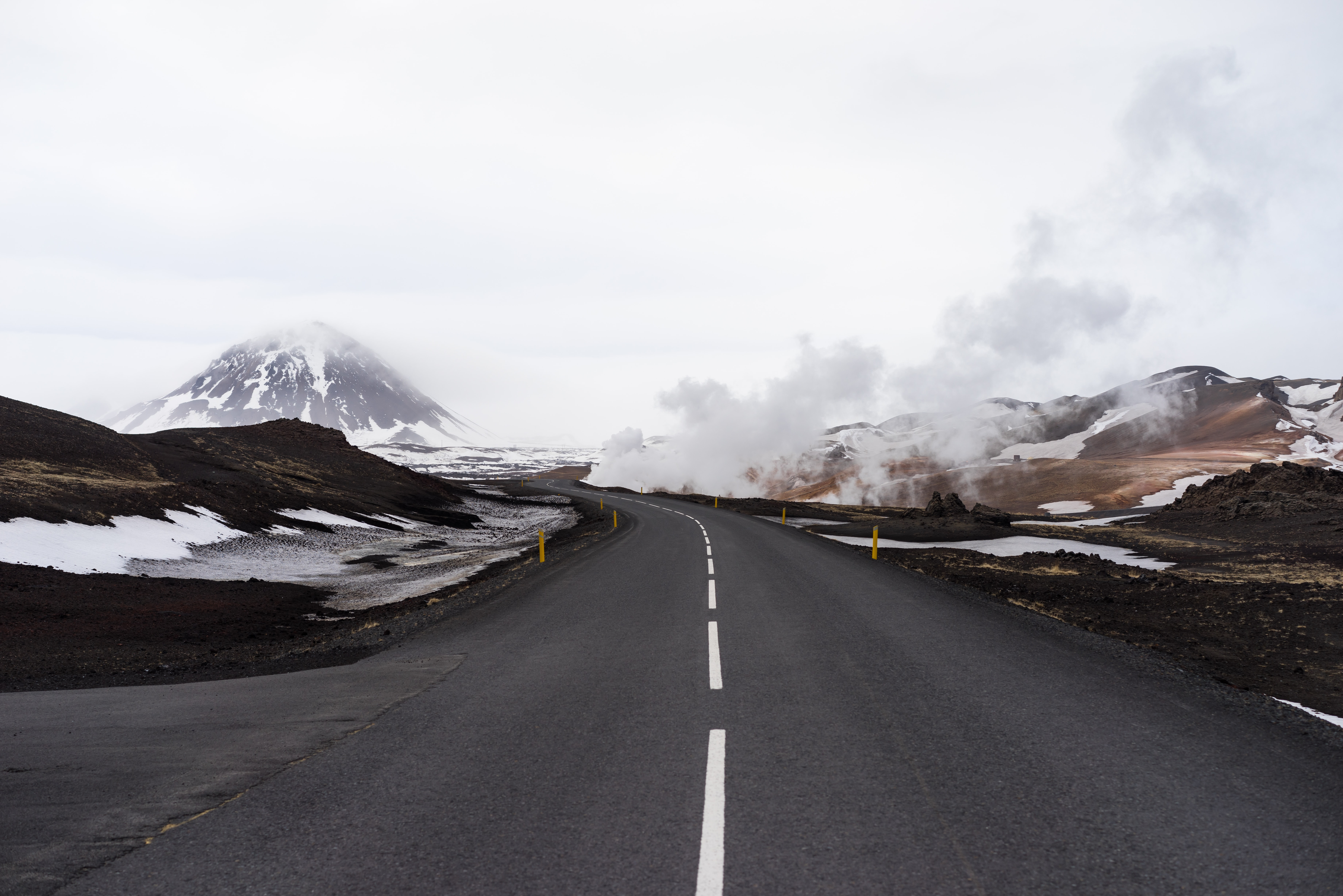 An asphalt road in the mountains with steam rising up on the roadside