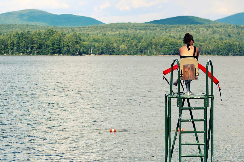 women sitting on chair watching body of water