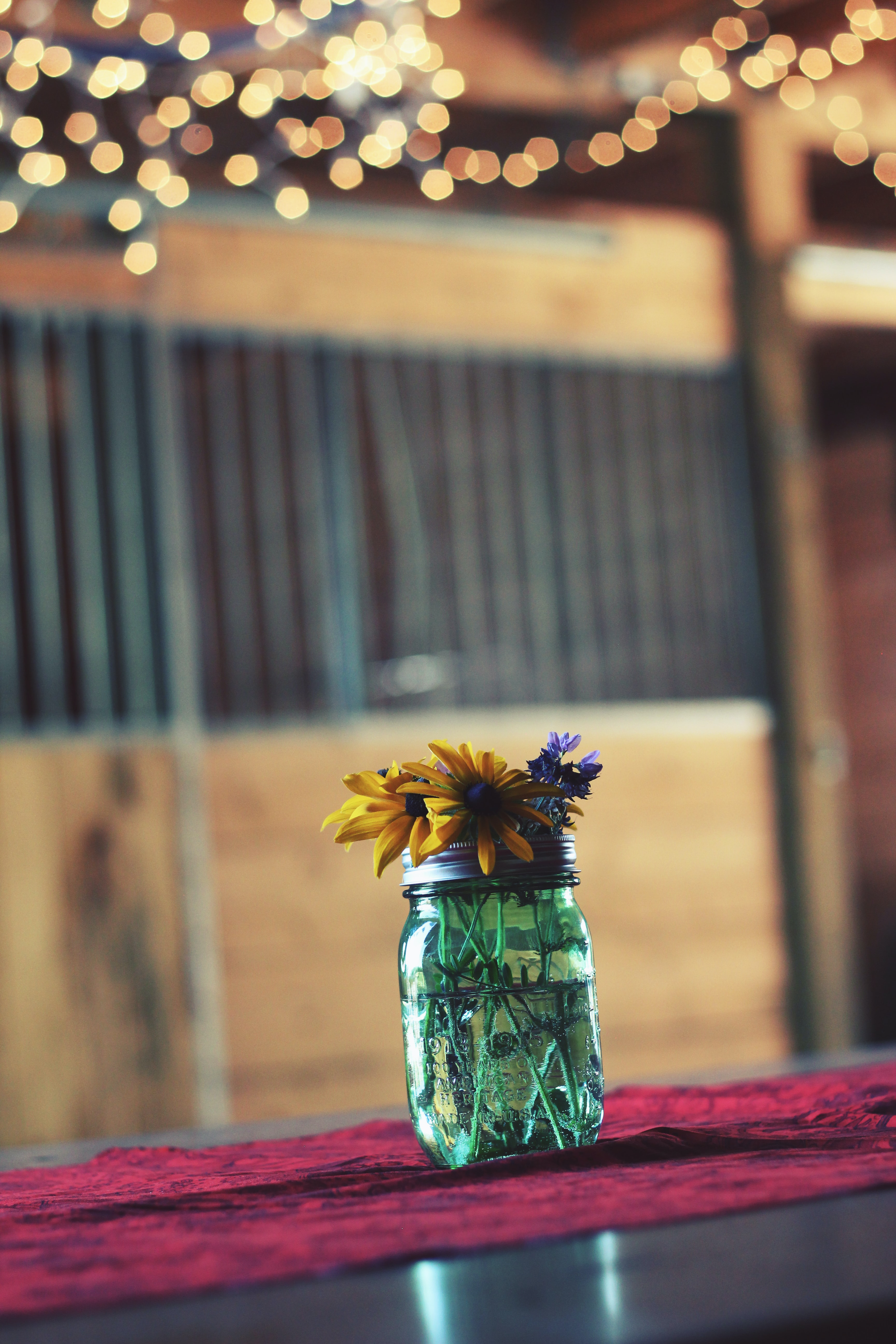 A glass jar with yellow and violet flowers on a wooden surface