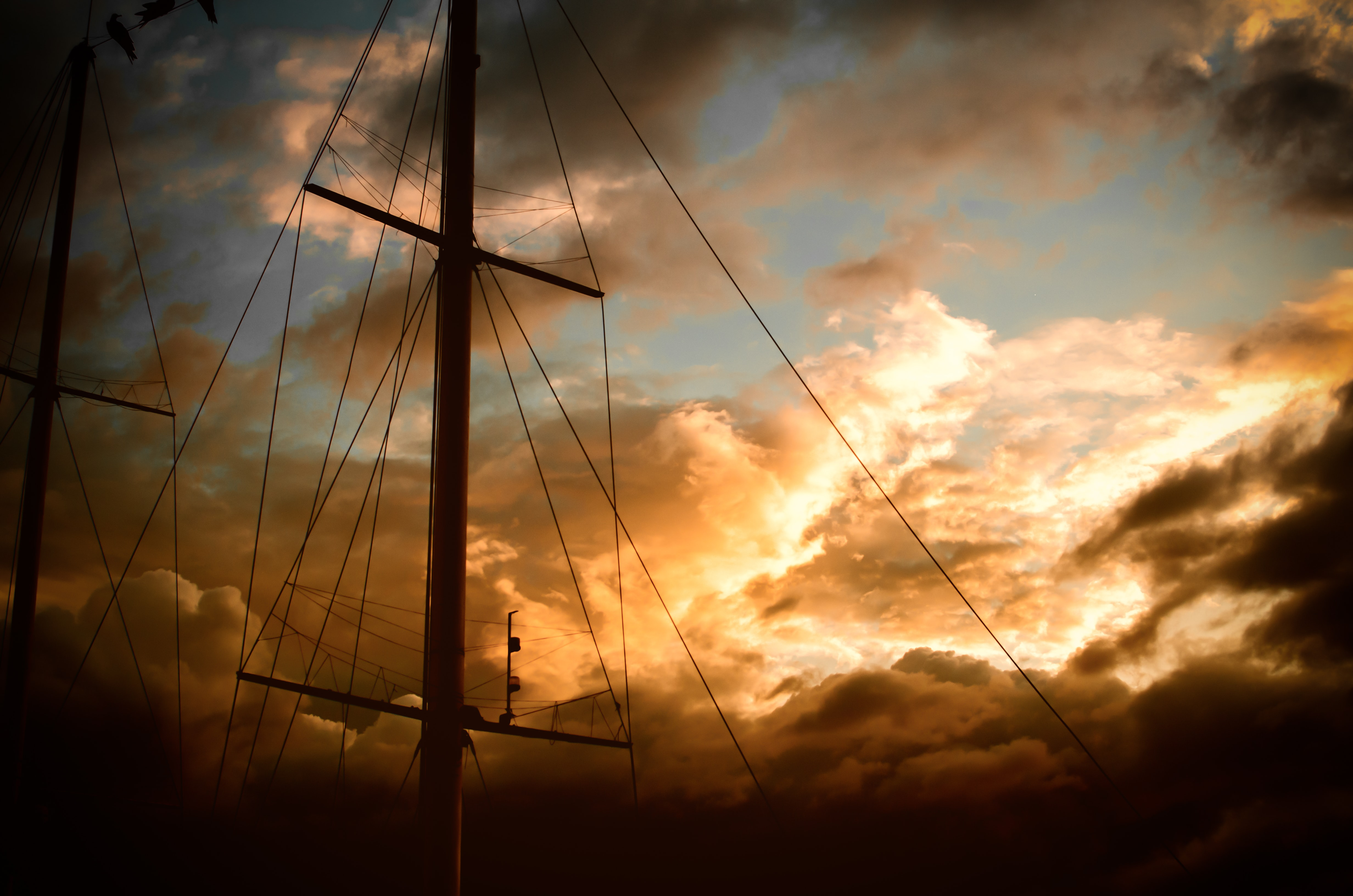 A ship's mast with rigging is set against golden clouds during sunset at La Paz.