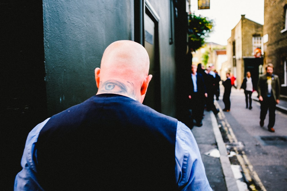 Bald man with a tattoo walks down a busy narrow street in Waterloo