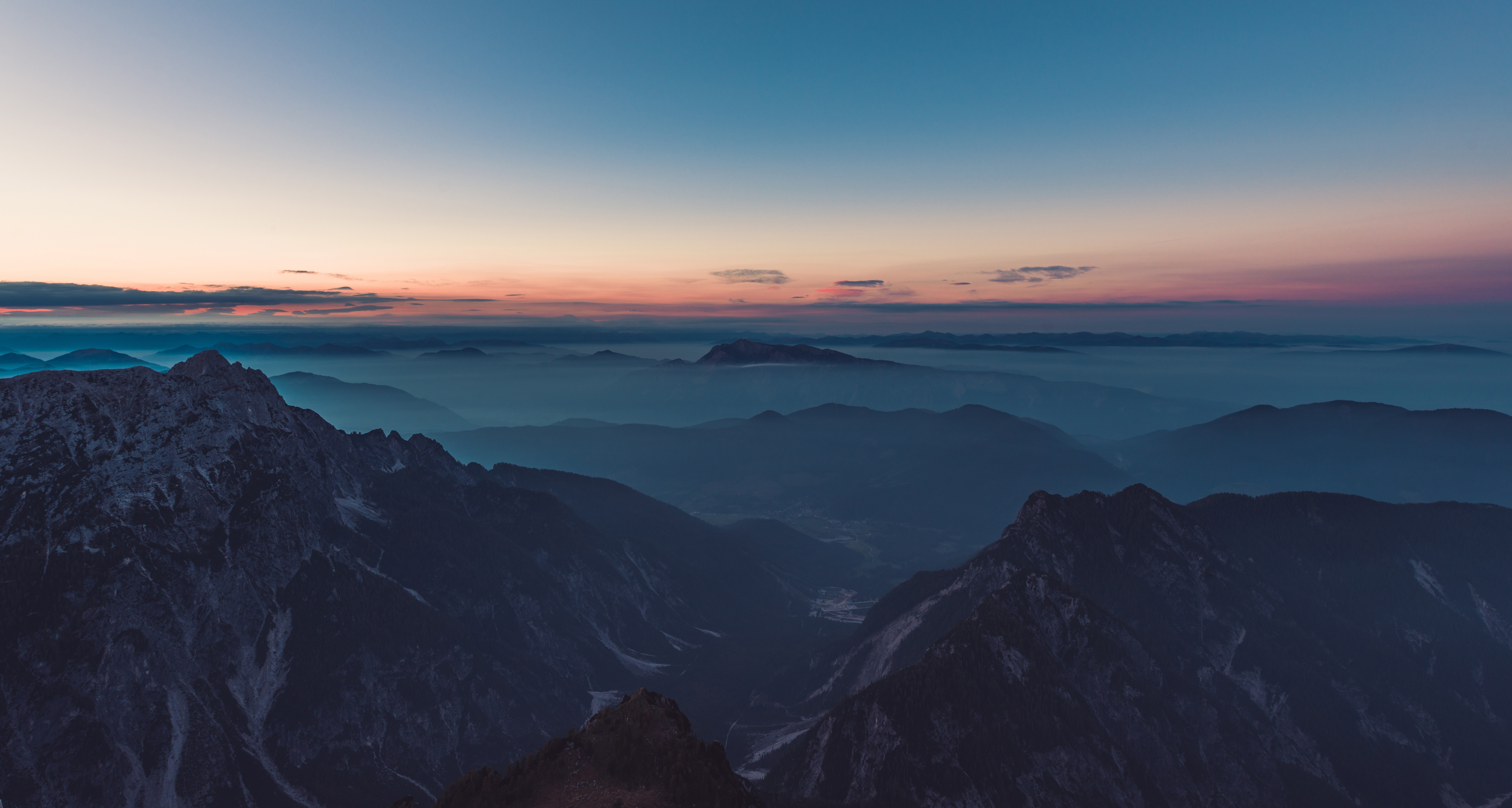 A hazy mountainous landscape with sharp ridges and deep valleys during sunset