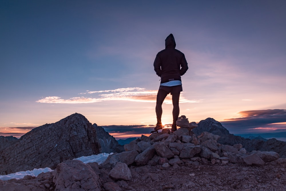 silhouette of person standing on rocks watching sunset