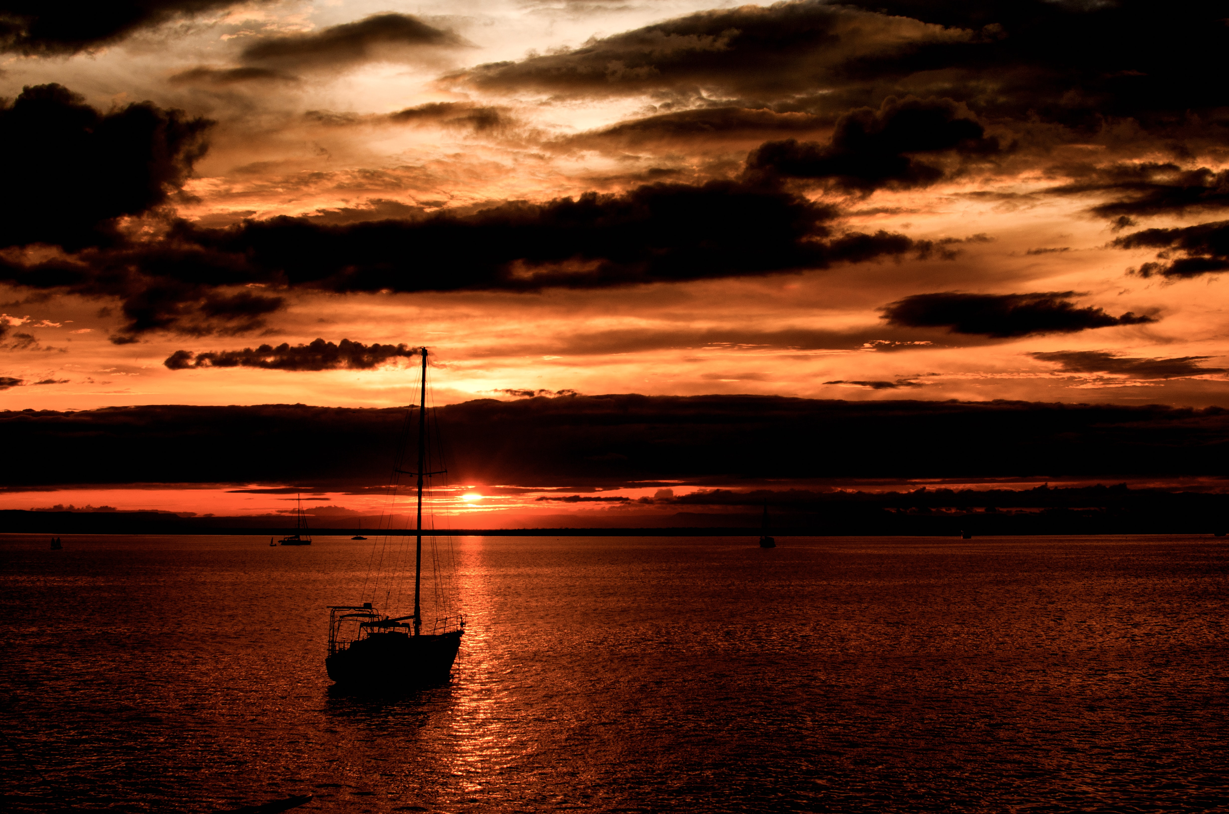 Small boats are set in silhouette as the sun sets in a deep orange across the water at La Paz.