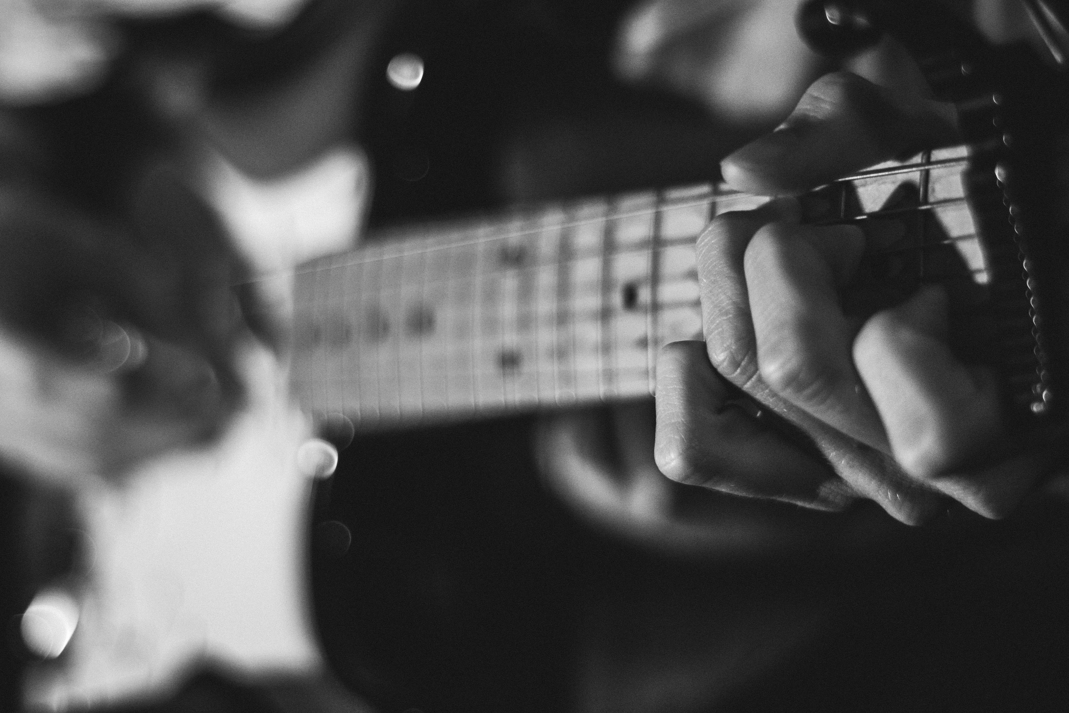 A black-and-white close-up of a guitar fretboard held by a player