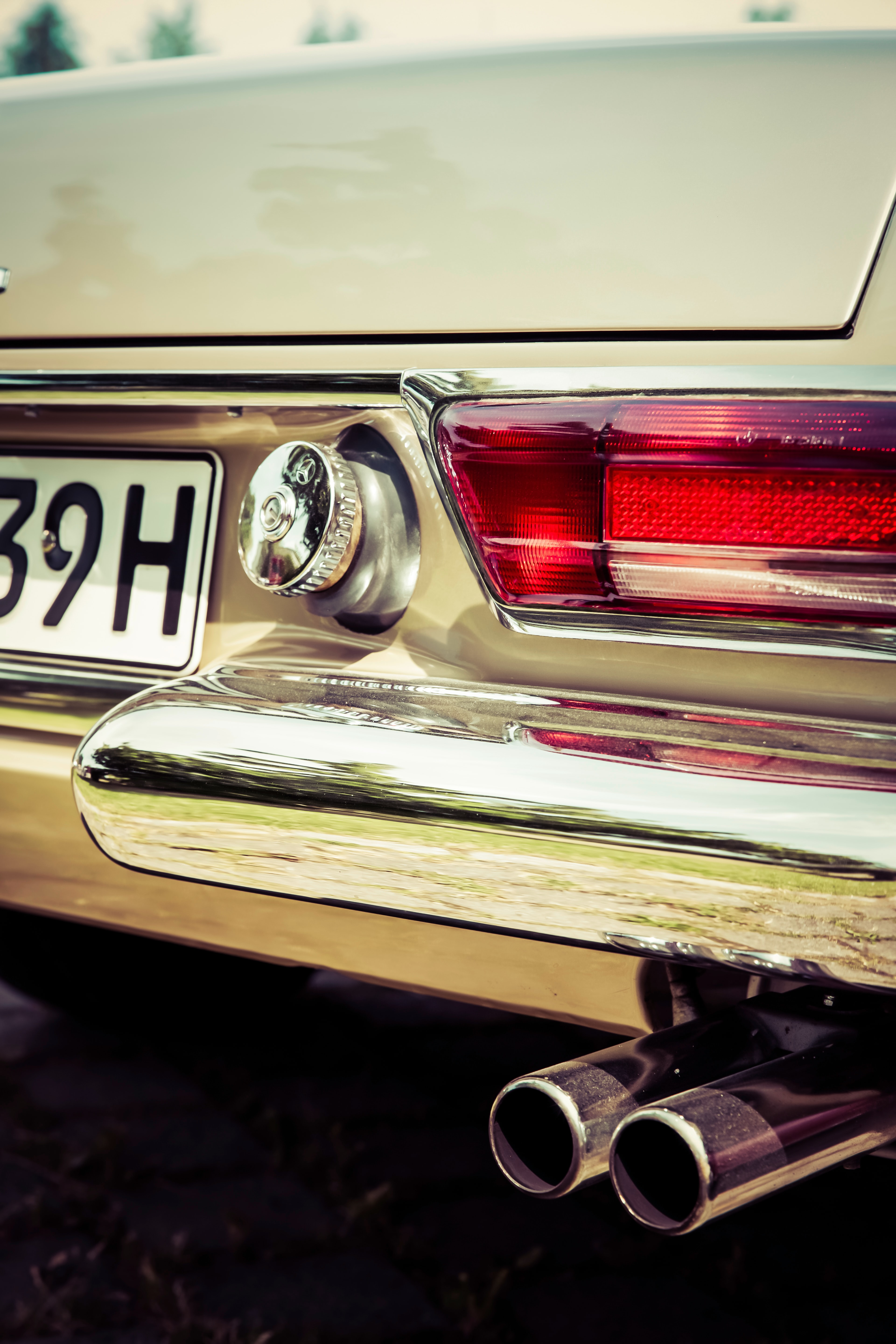 Macro view of the back of a vintage car's tail light and exhaust pipe.