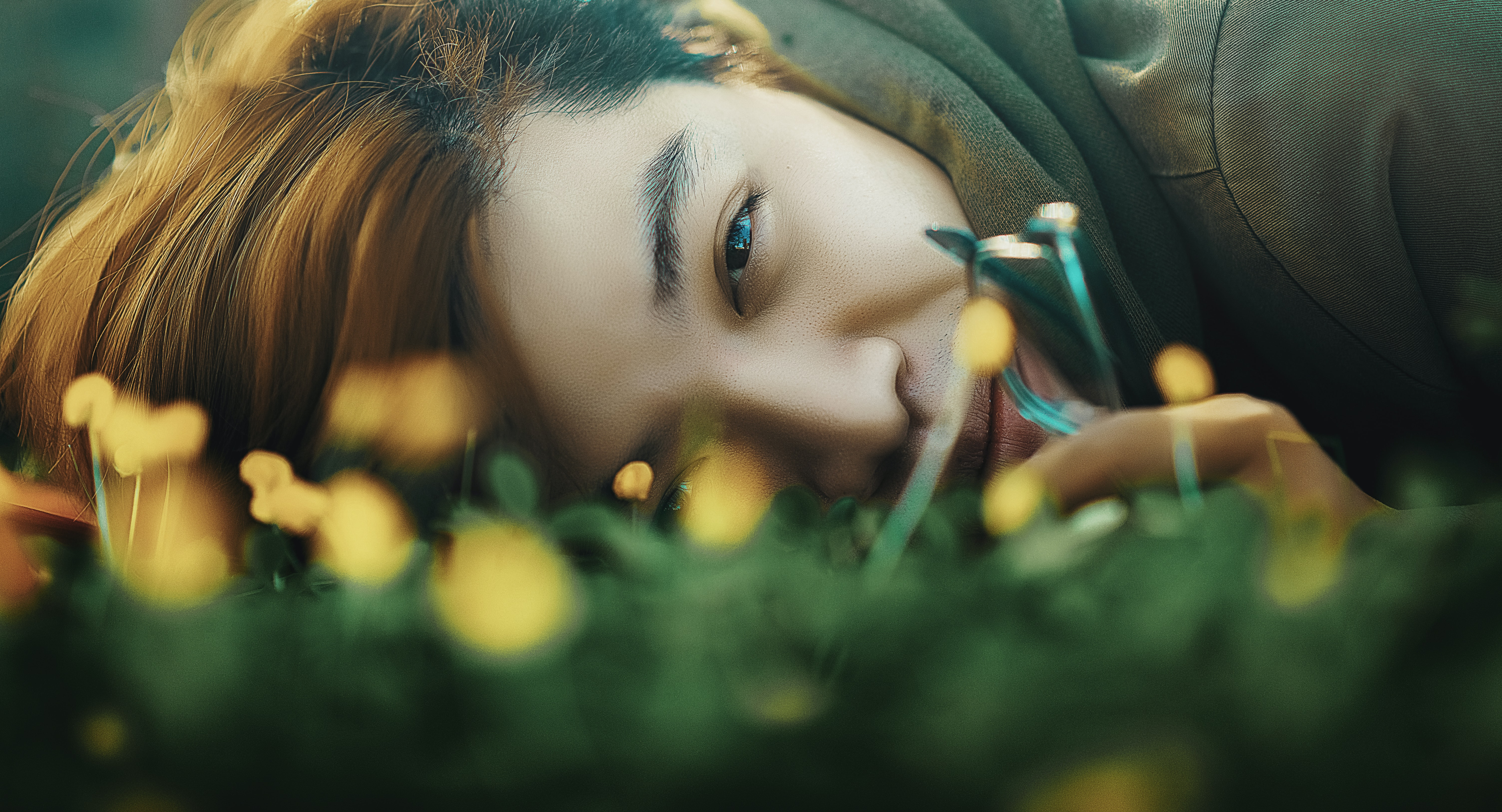 An Asian man lying on the ground looking at the camera.