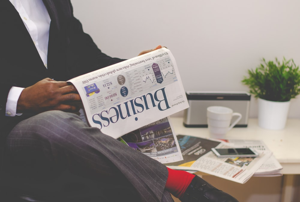 person sitting near table holding newspaper