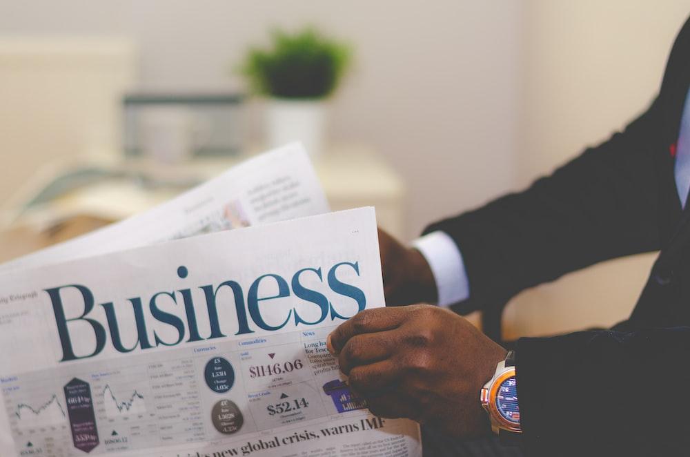 A businessman opening a business newspaper